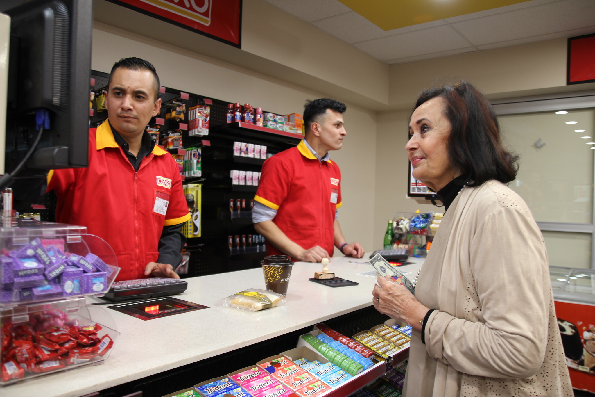 """A customer buys some coffee and a sandwich at """"Oroxxo"""" with her Orozco dollars at the opening of the show."""