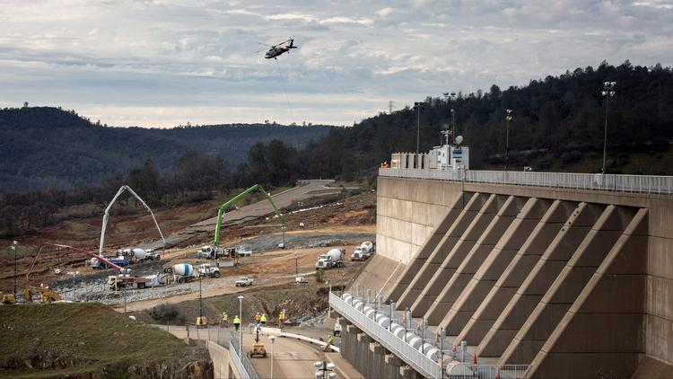 Reconstruction continued Wednesday in a race to shore up the emergency spillway, left, at the Oroville Dam. (Brian van der Brug / Los Angeles Times)
