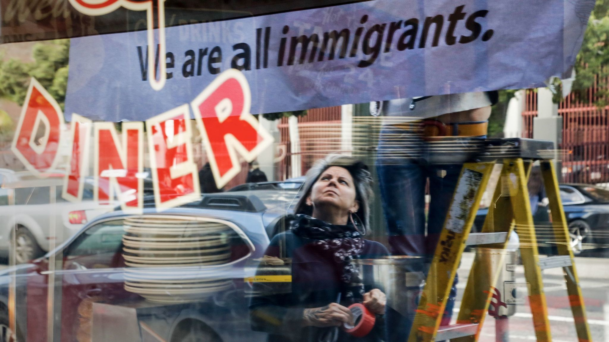 """After closing their restaurant for the day, Monica May watches while her partner Kristen Trattner hangs a sign above their Nickel Diner in Downtown Los Angeles in solidarity with a national """"Day Without Immigrants."""""""