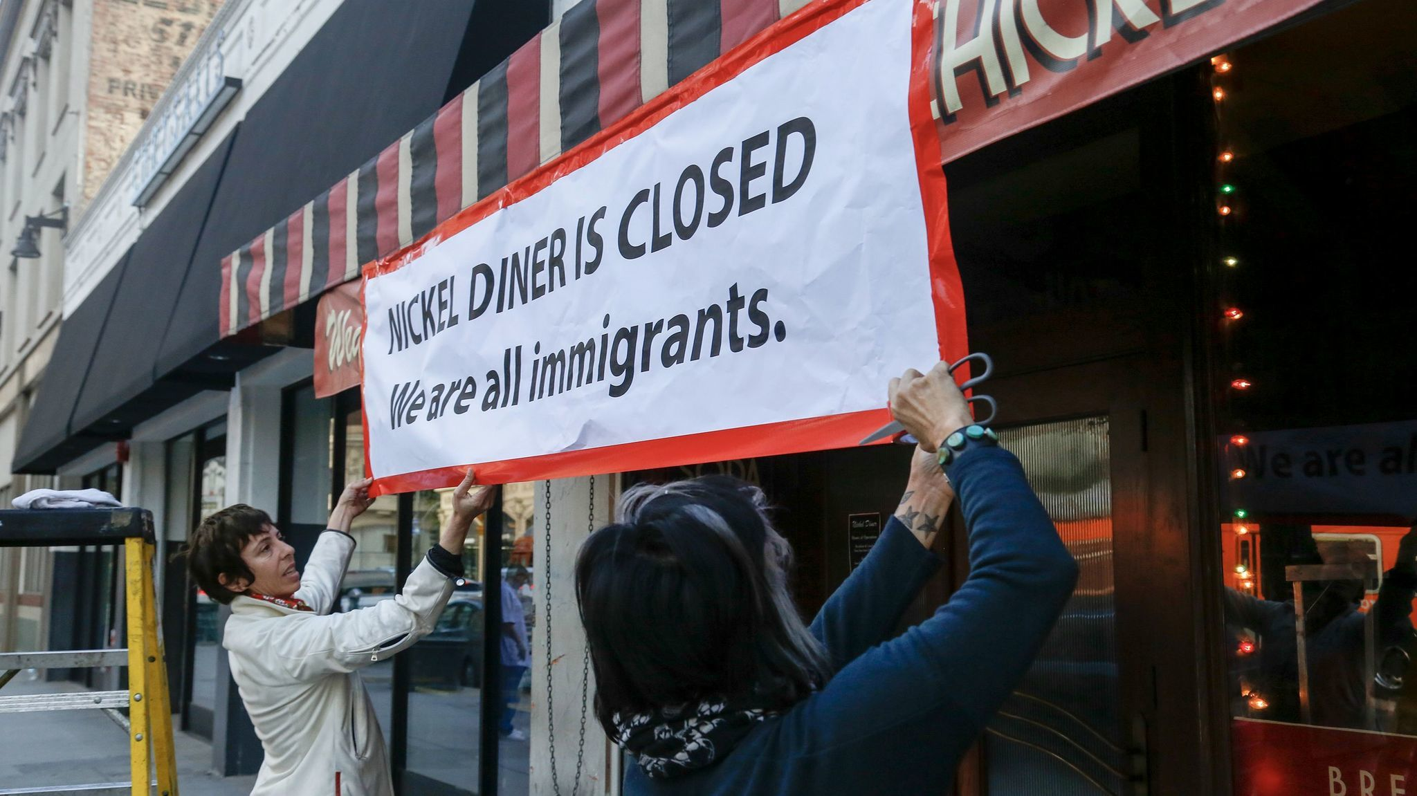 """The co-owners of the Nickel Diner, Kristen Trattner (left) and Monica May closed their restaurant for the day in Downtown Los Angeles and hung a large sign over the door in solidarity with a national """"Day Without Immigrants."""""""