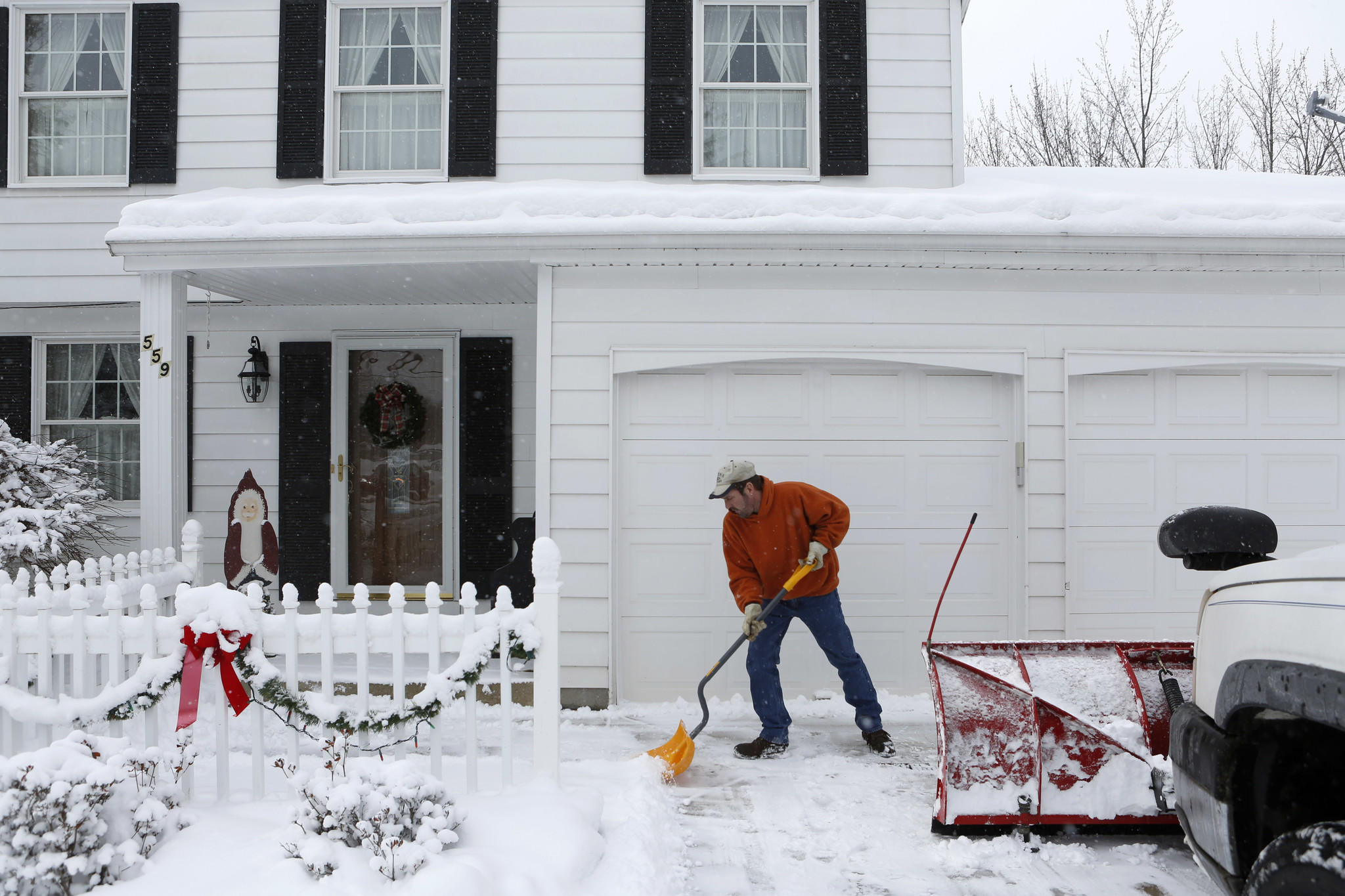 After shoveling a client's driveway, Chris Wade shovels the walkway. Wade worked at Delphi Automotive Systems for 13 1/2 years before taking a buyout in 2006 as part of the company's ongoing shift of production out of the U.S.