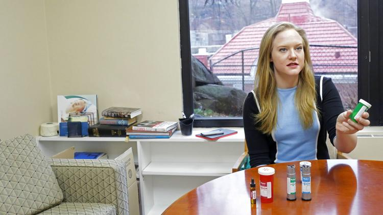 Hillary Peckham, of the medical marijuana dispensary Etain Health, shows marijuana tincture, capsules and vaporizer cartridges at the Hebrew Home in New York on Feb. 7, 2017.
