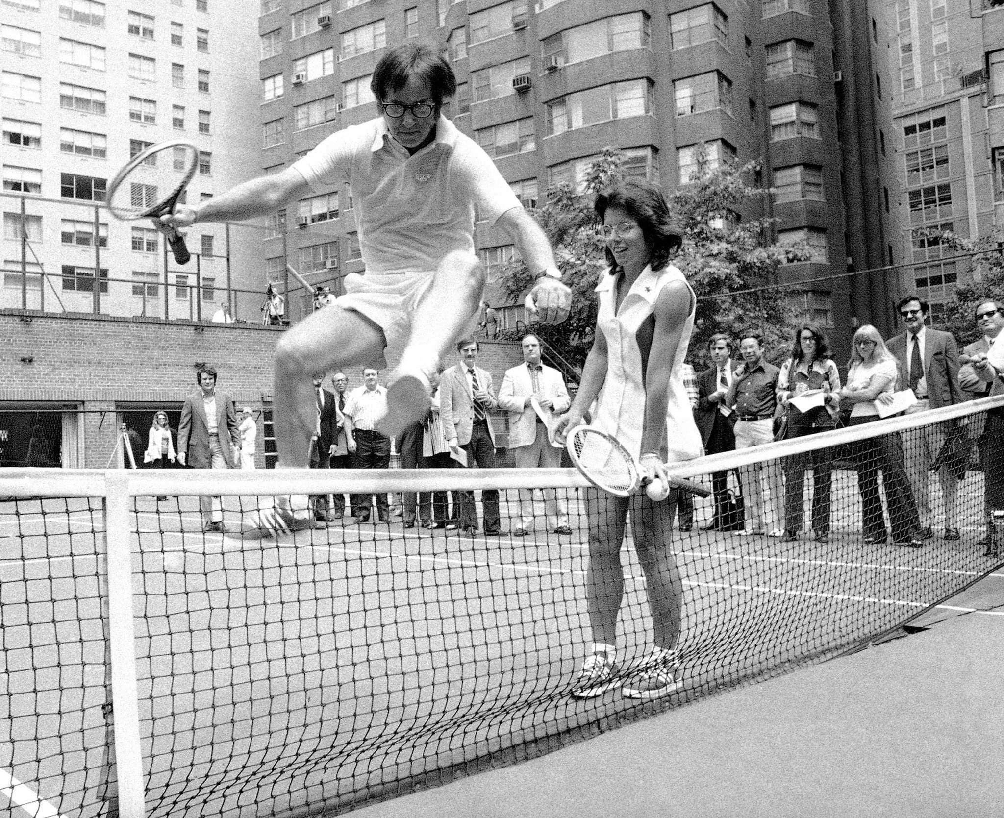 Billie Jean King holds down the net for a jumping Bobby Riggs. The two went head-to-head not only on the court but in the media storm leading up to the match.