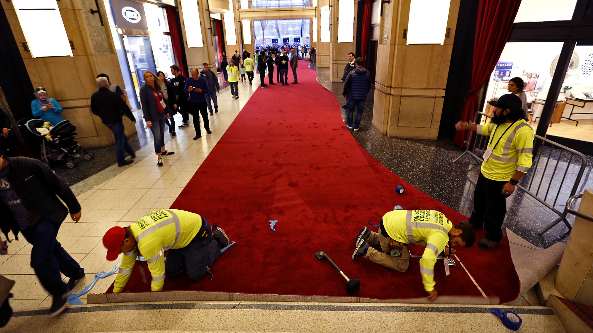 Alvarado Contreras, from left, Rene Palma and Edgar Ochoa cut into place a roll of red carpet in the Dolby Theatre's forecourt.