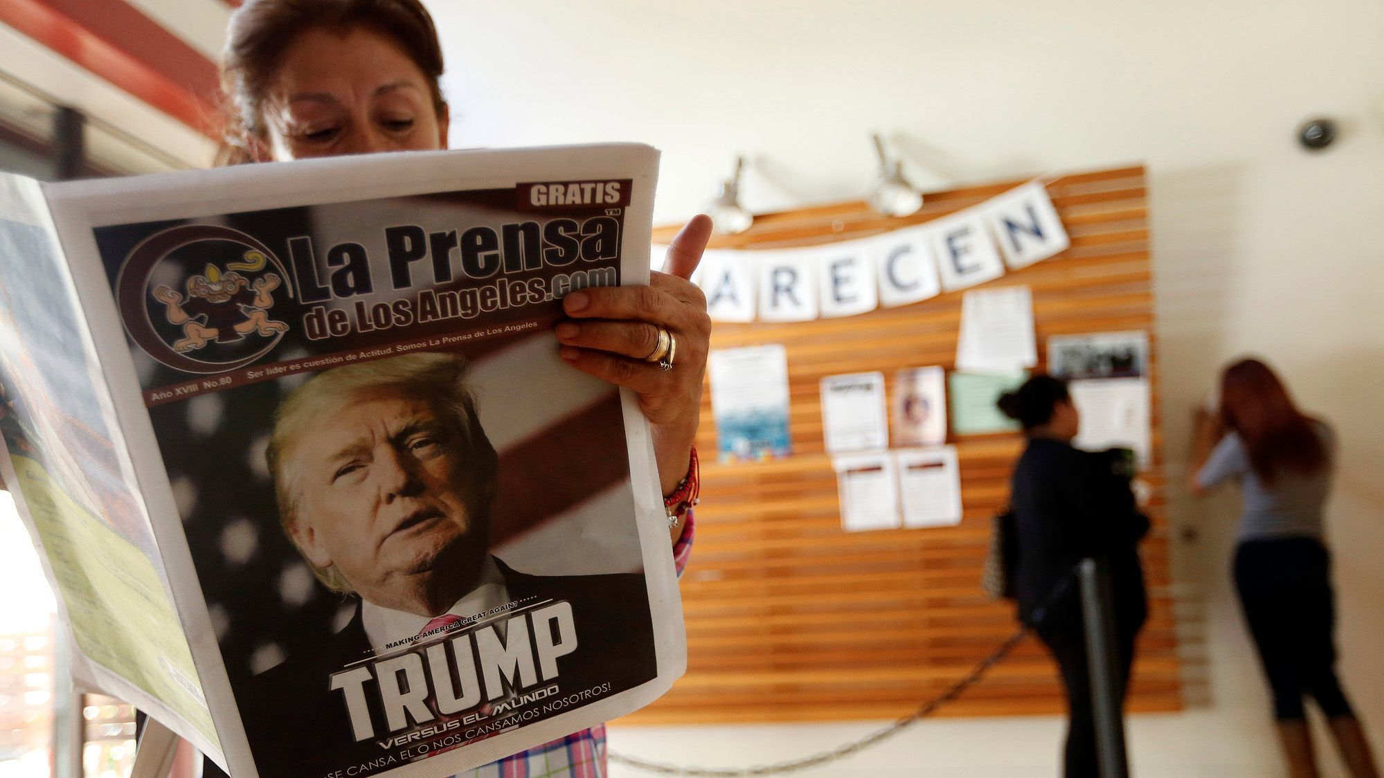 Vences Olivia, 52, reads a local newspaper while waiting for legal counsel at the Central American Resource Center.