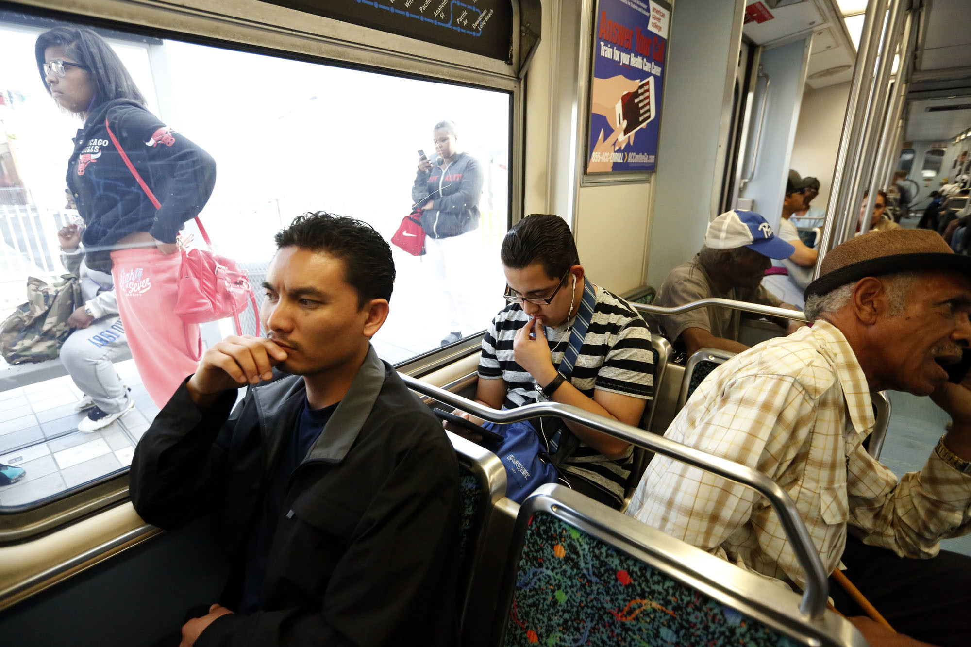 Phal Sok, 35, left, rides the Metro Blue Line train in Los Angeles to visit with his brother in Long Beach.