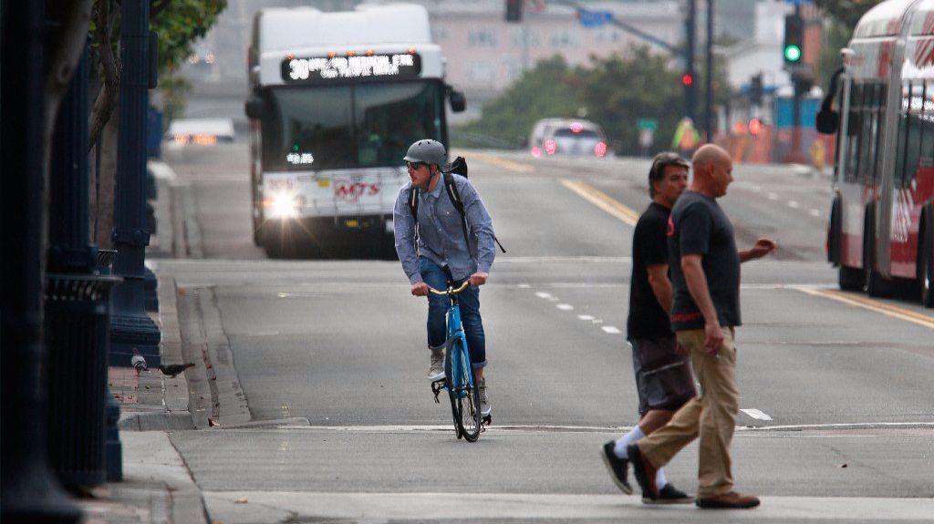 Van Gould rides his bicycle down Broadway while commuting to work at Symphony Towers.