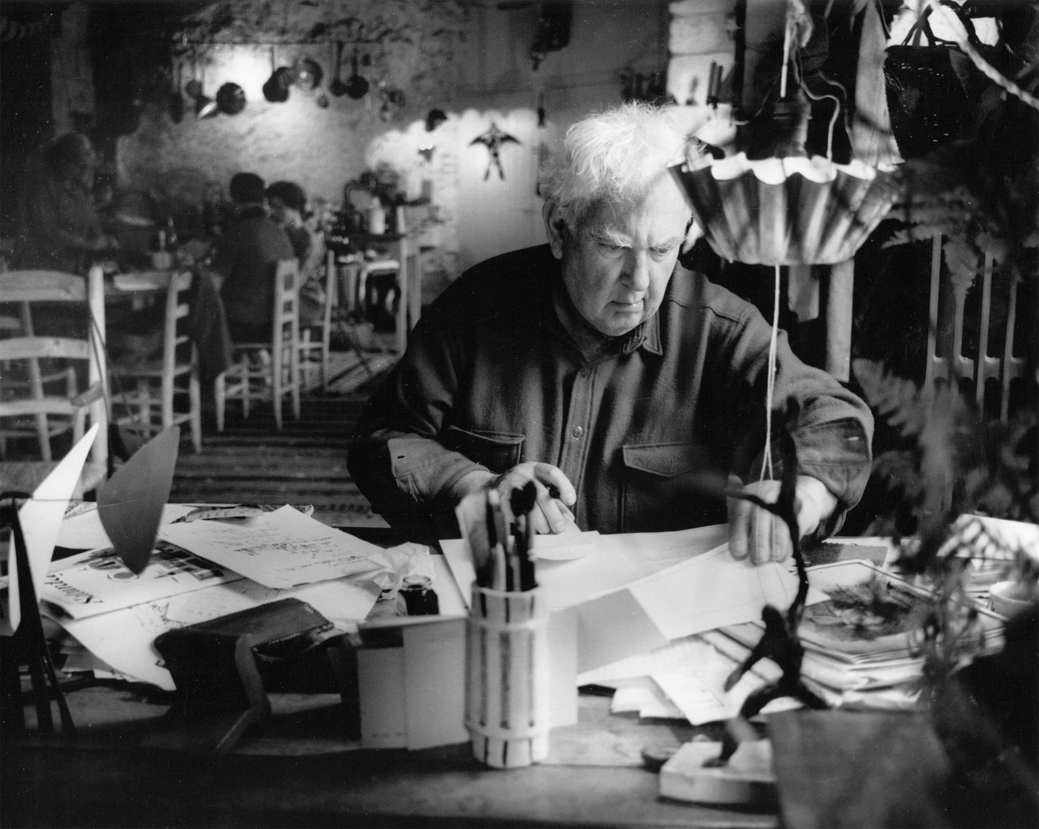 Alexander Calder answers his mail in Saché, France, in 1965 — from an exhibition of the artist's photographs at Edward Cella Art + Architecture.