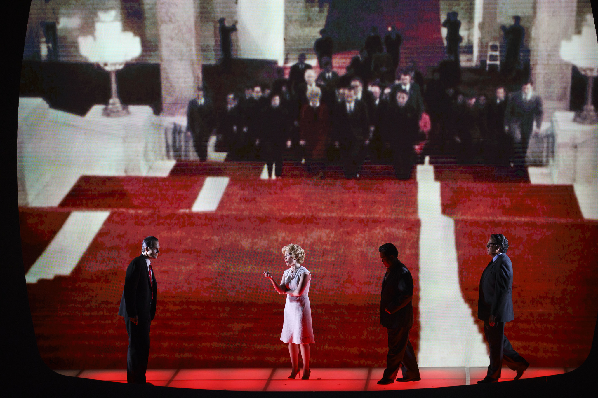 The live cast in the foreground, echoed by historical footage in the background.