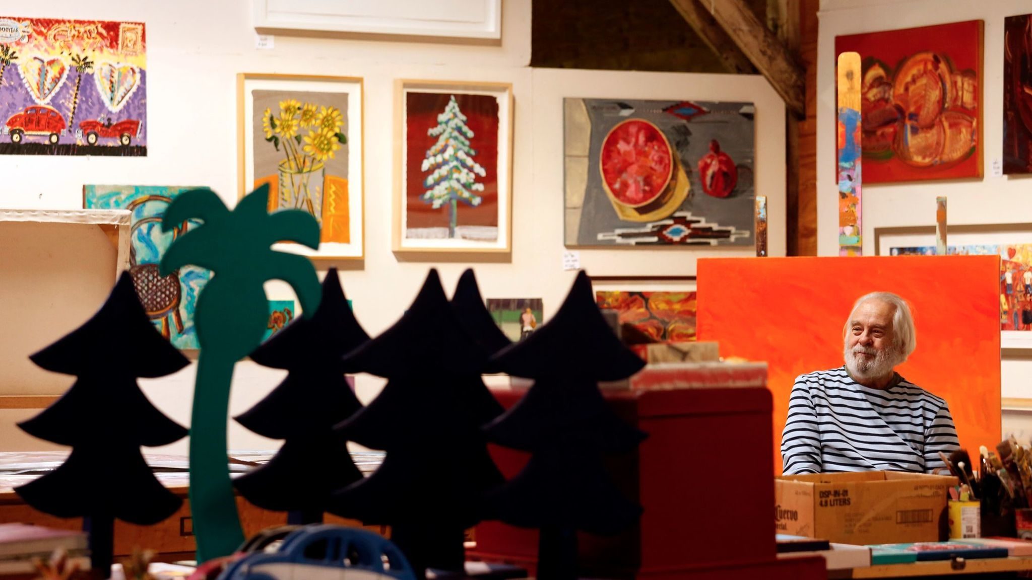 Frank Romero sits among his paintings and various works in progress in his sprawling Los Angeles studio.