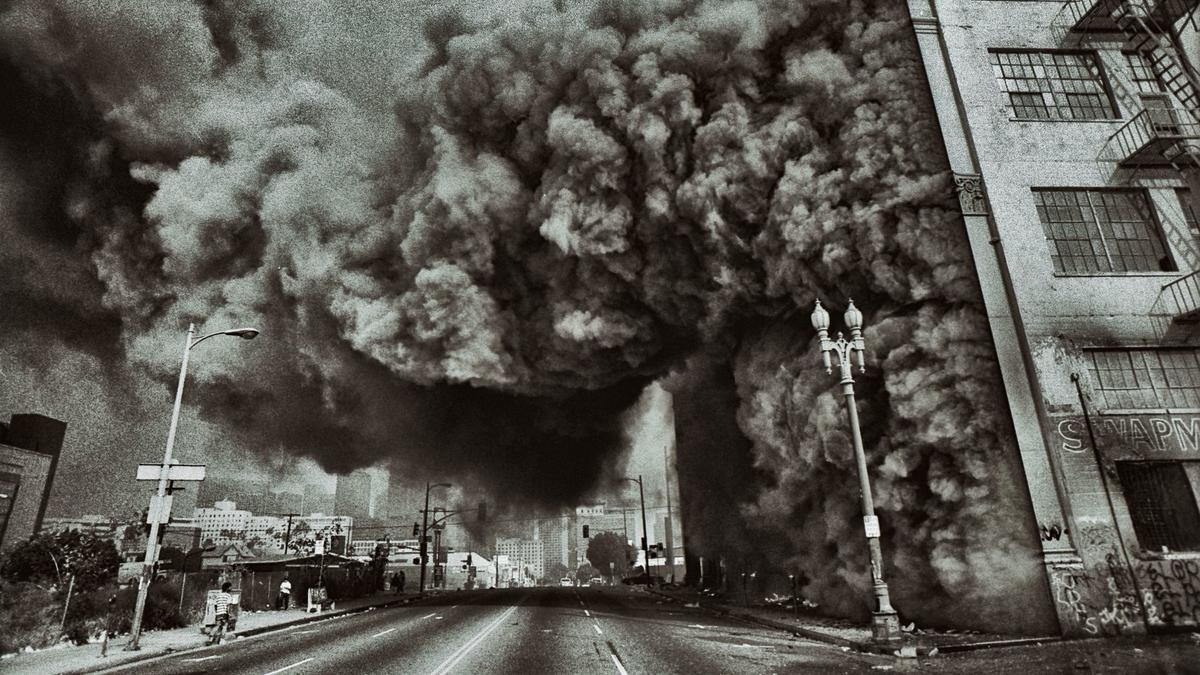 A building at 7th Street and Union Avenue in Los Angeles goes up in flames during the 1992 riots, the subject of an exhibition at the California African American Museum.