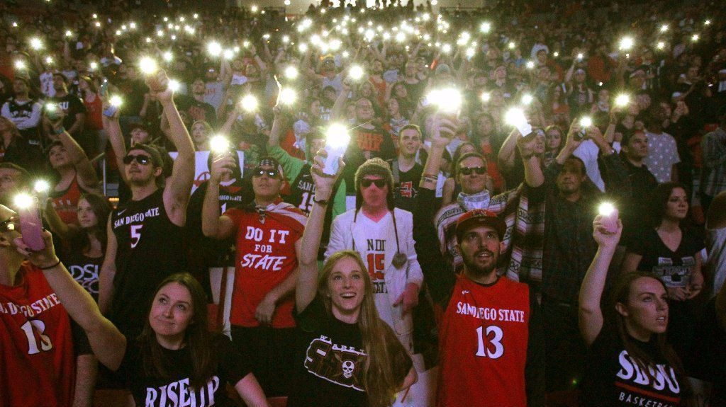 Aztecs' fans hold lights in the darkened arena as their team is introduced for the game.