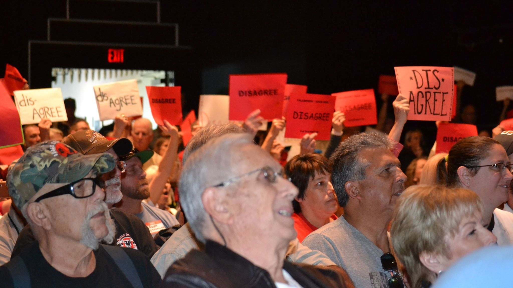 """Many inside the Ramona Mainstage hold up signs saying """"disagree"""" in response to a comment made by Congressman Duncan Hunter."""