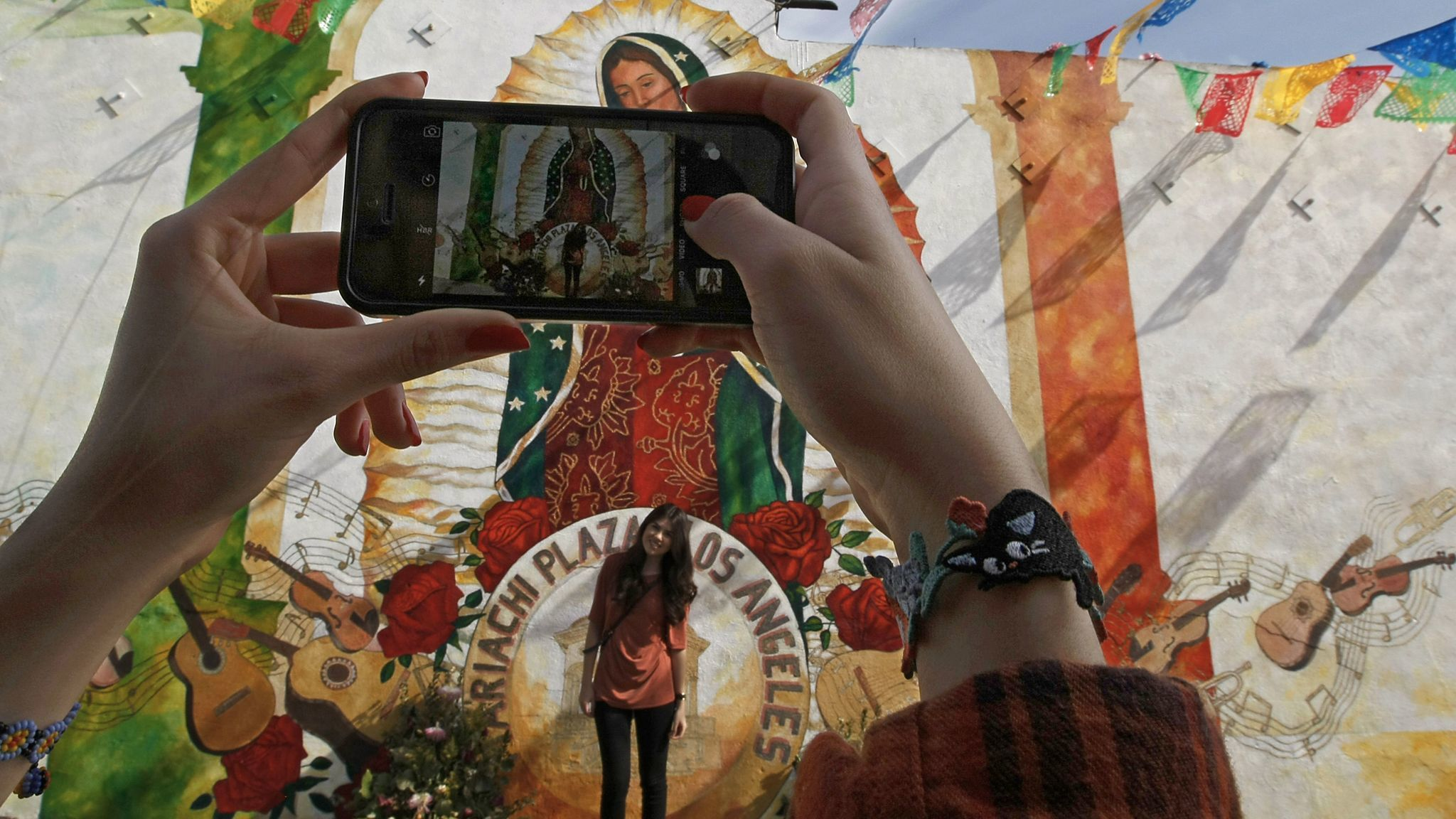 Jessica Alvarez takes a photo of Briana Alvarez on a visit to Mariachi Plaza in Boyle Heights.
