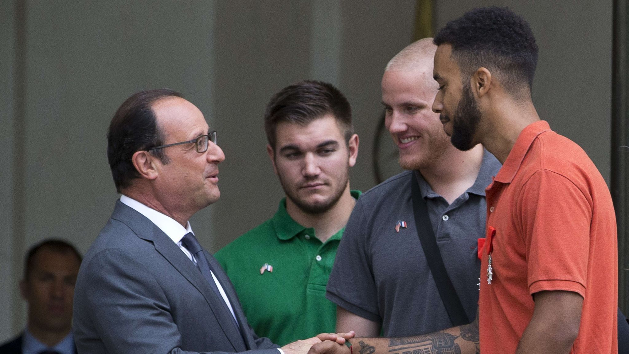 French President Francois Hollande, left, shakes hands with Anthony Sadler next to off-duty U.S. servicemen Spencer Stone, second from right, and Alek Skarlatos, considered heroes for their bravery after they overpowered an attacker on a train from Amsterdam to Paris.