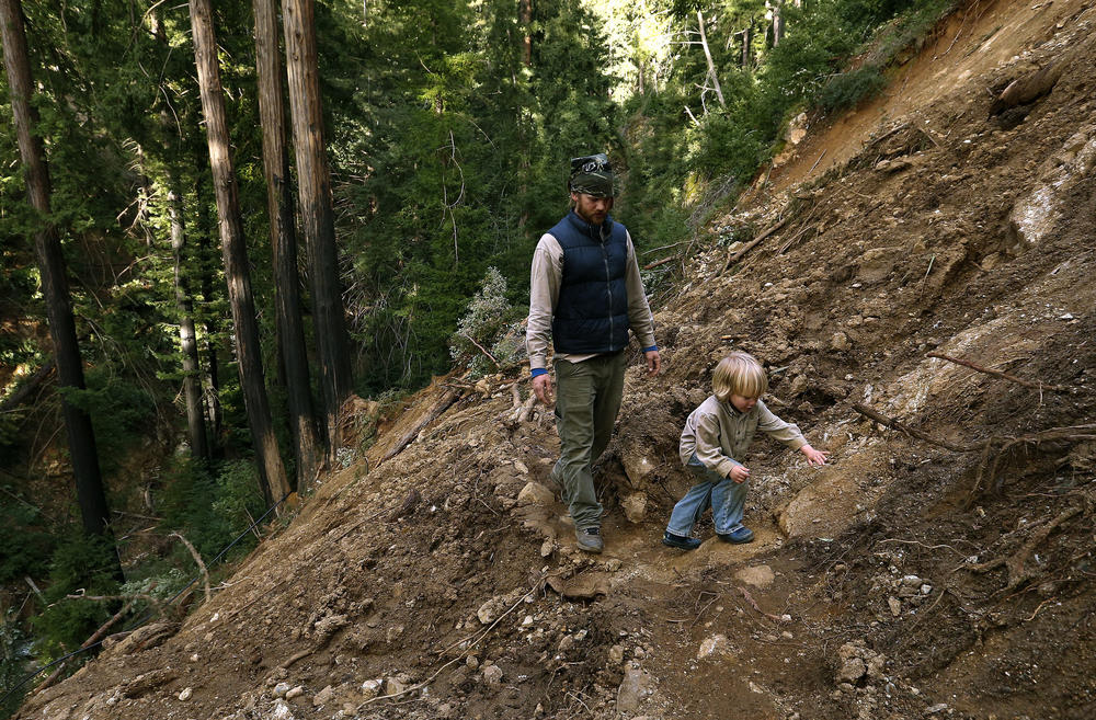 With the road taken out by a massive landslide, Big Sur resident Scott Moffat and his son Roman, 4, hike through muck and debris above the Ventana Inn to get to their truck.