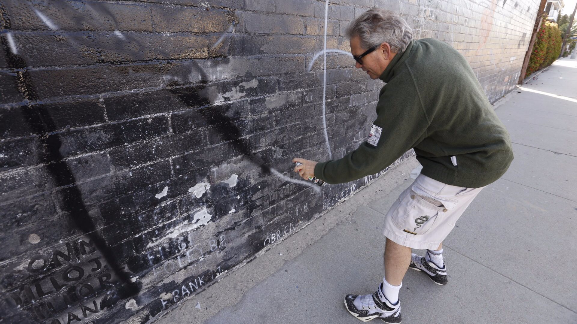 Steven Barber uses black spray paint to cover the white letters of graffiti on the wall.