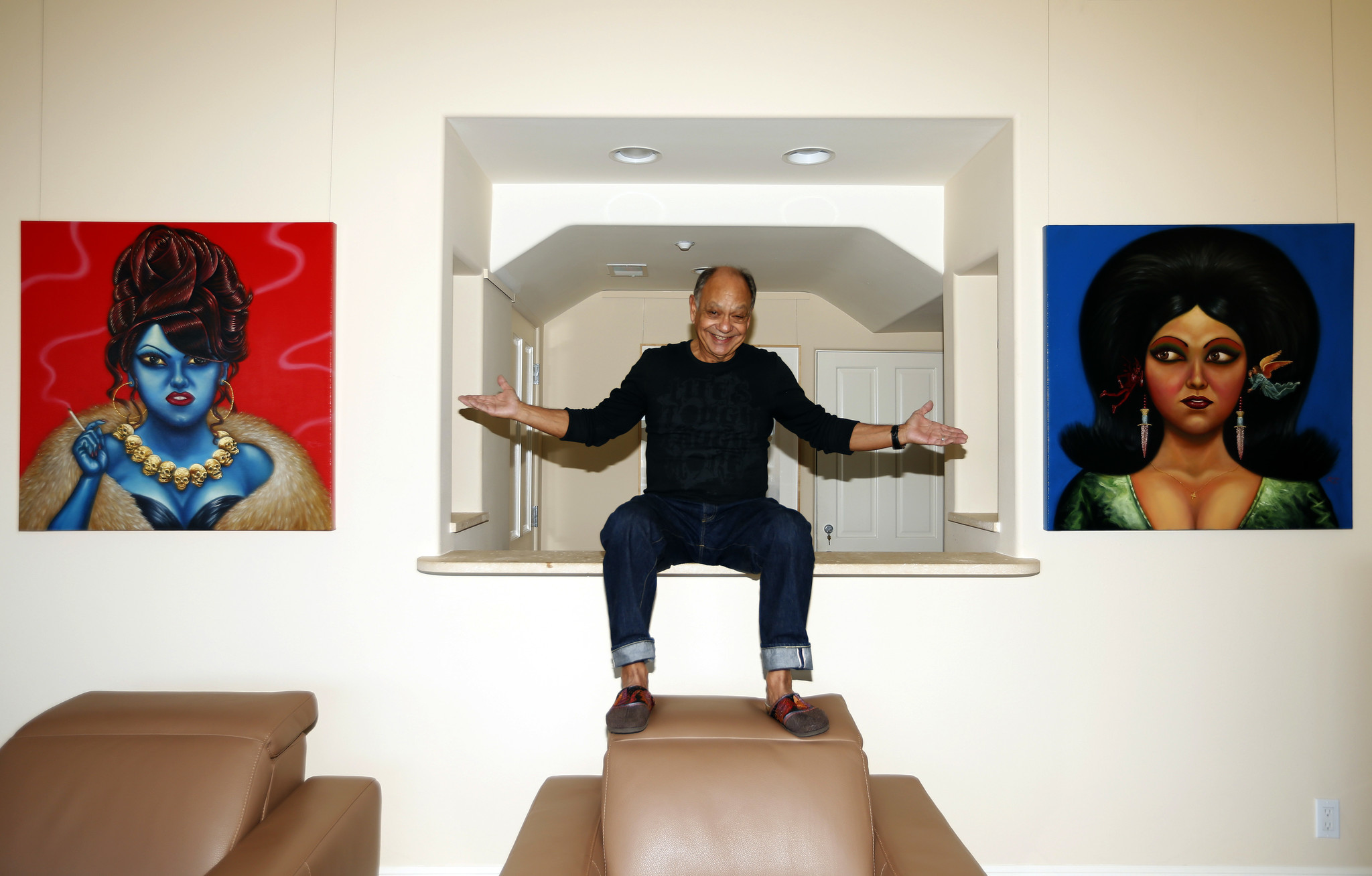 A noted art collector, Cheech Marin is flanked by a pair of paintings by Ricardo Ruiz in his Pacific Palisades home.