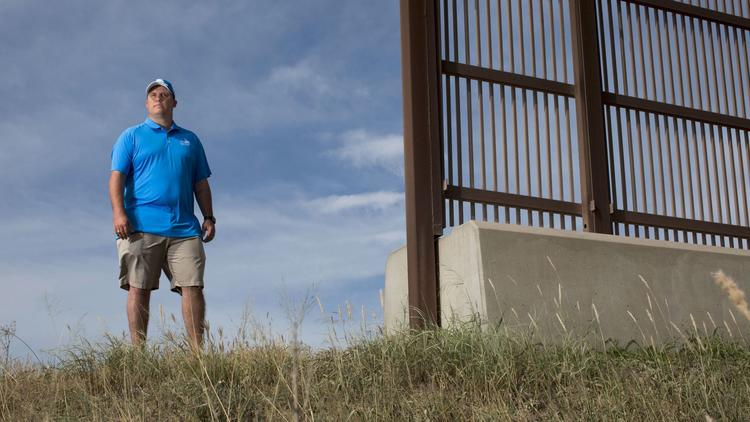 Jeremy Barnard, general manager of River Bend Resort & Golf Club stands at the existing border wall