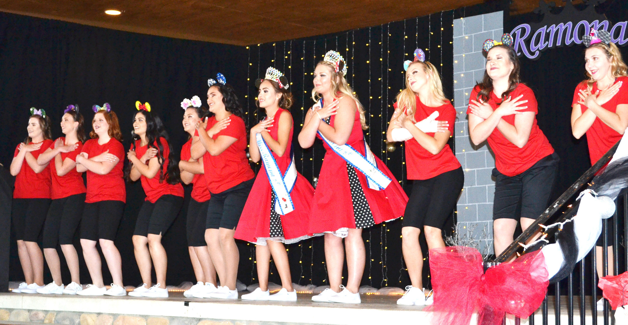 2016 Miss Ramona Chersten Sandvik and Teen Miss Ashley Dominguez, wearing dresses, and Miss Ramona and Teen Miss contestants perform the opening dance routine in the Disney-themed pageant. The contestants wear Mickey Mouse ears that they decorated.