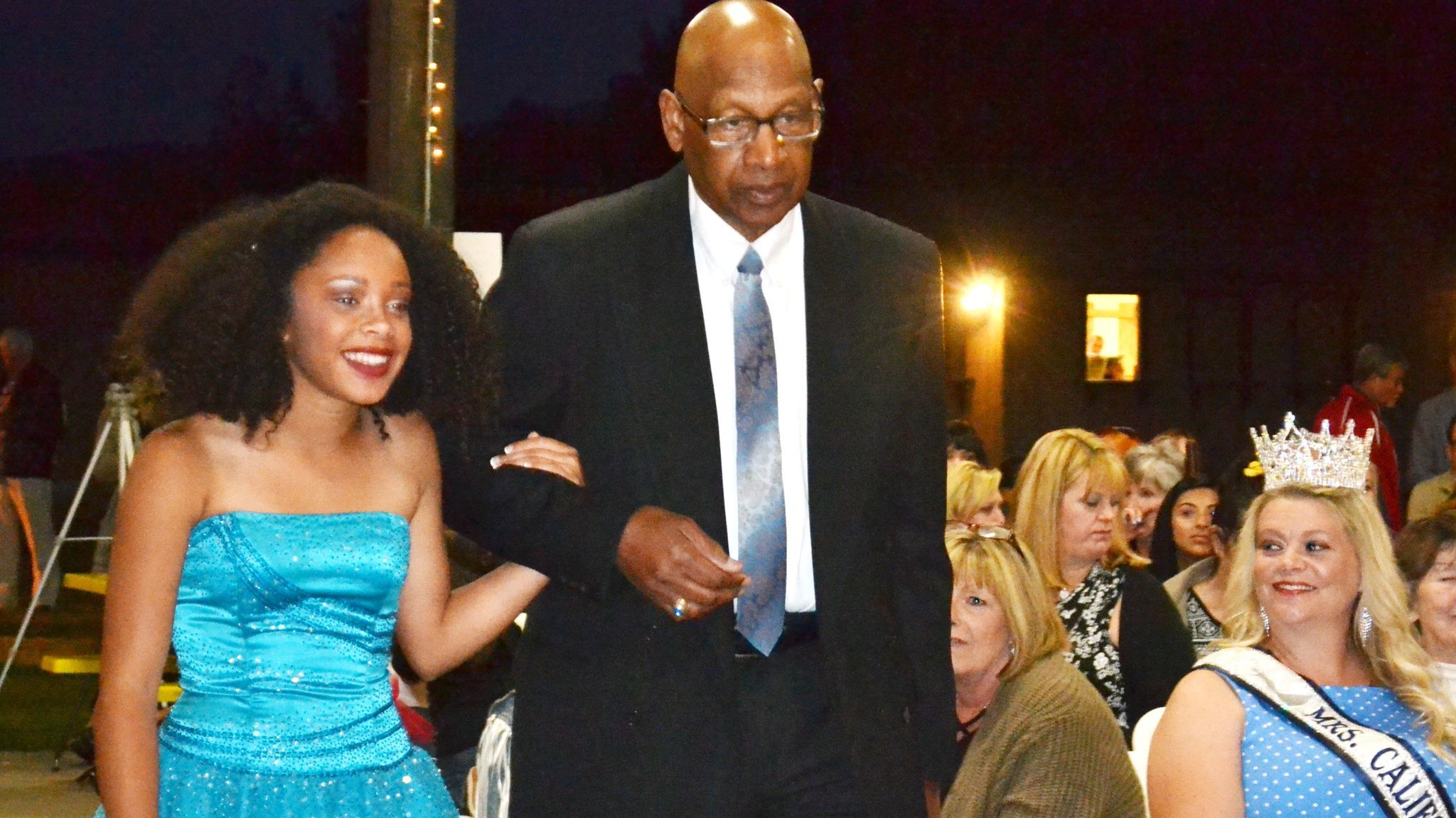 Teen Miss contestant Erika Bradley is escorted by her grandfather, Leon Simms, during the evening gown portion of the pageant.