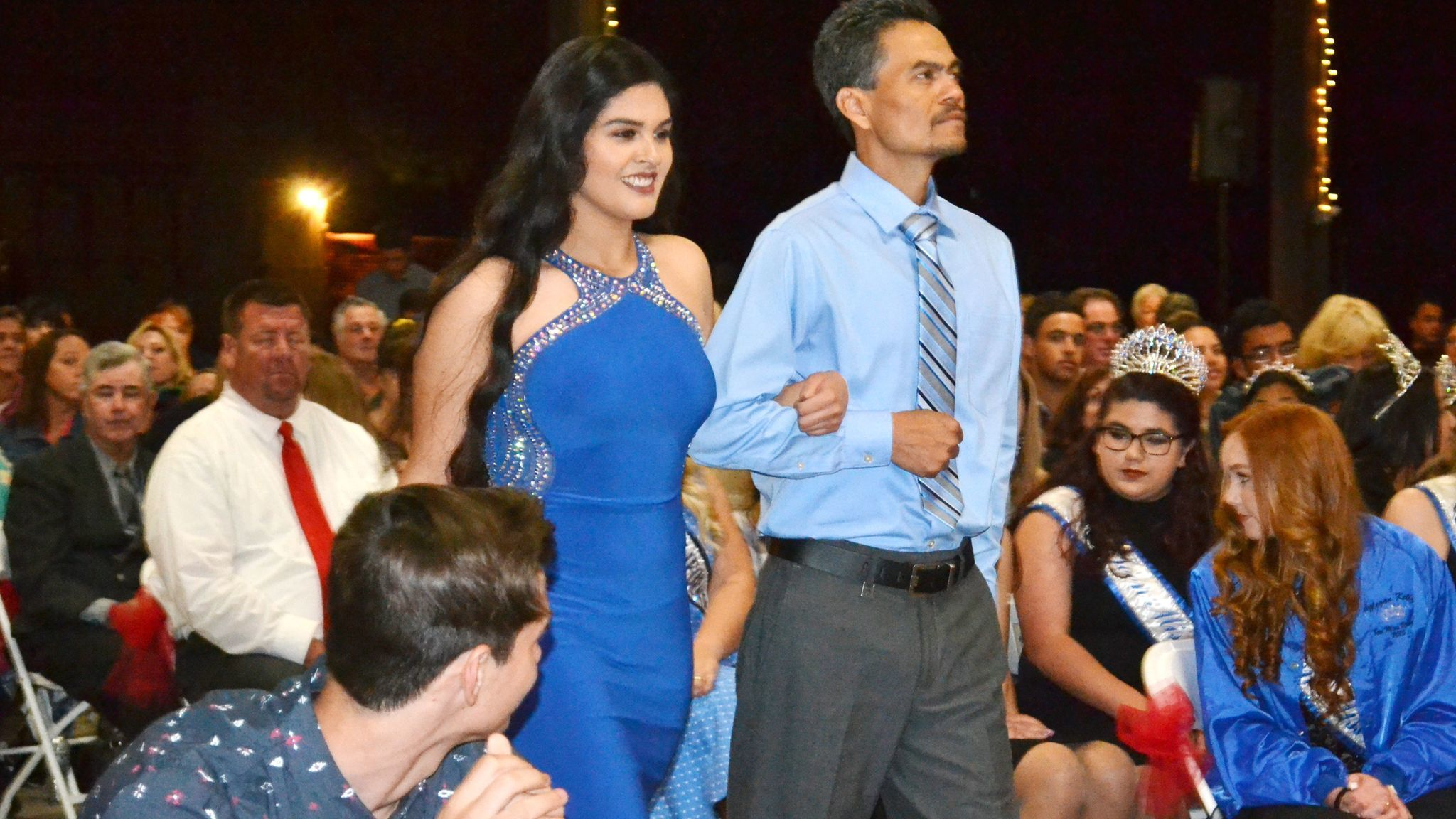 Miss Ramona contestant Mariana Gonzalez-Lopez, escorted by her stepfather, Miguel Busto, walks down the aisle in her evening gown.