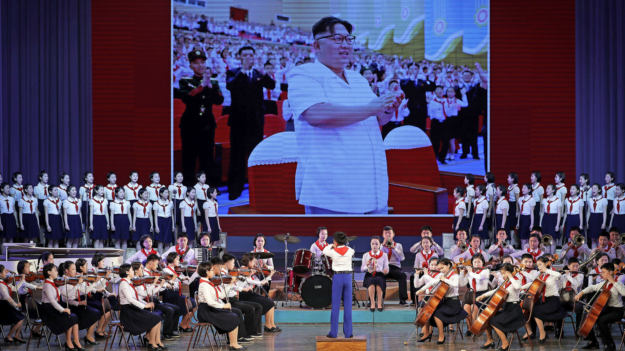 Young North Korean musicians perform against a backdrop image of leader Kim Jong Un.