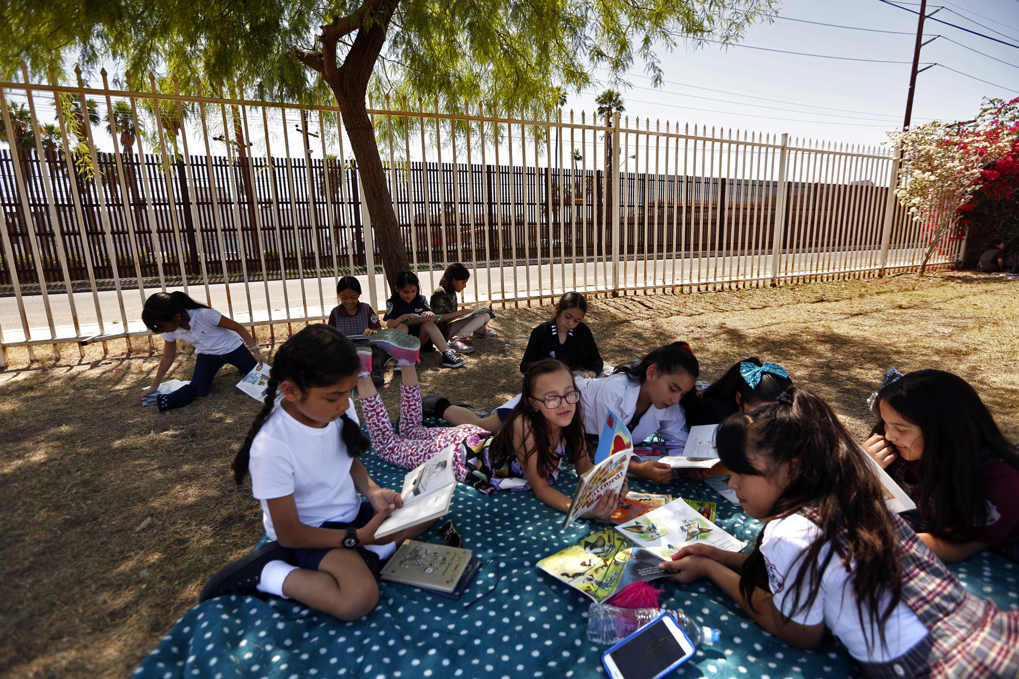 Third-graders read under the shade of tree at the Calexico Mission School against a backdrop of the border fence, in brown, in Calexico, Calif.