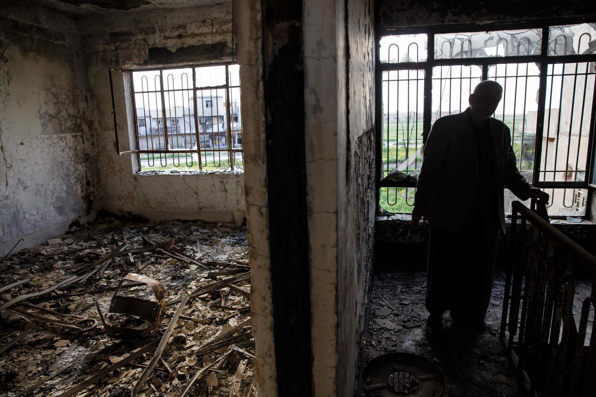 Tawfiq Abosh Jabu Sakar wanders through his home destroyed by Islamic State in Qaraqosh, Iraq.