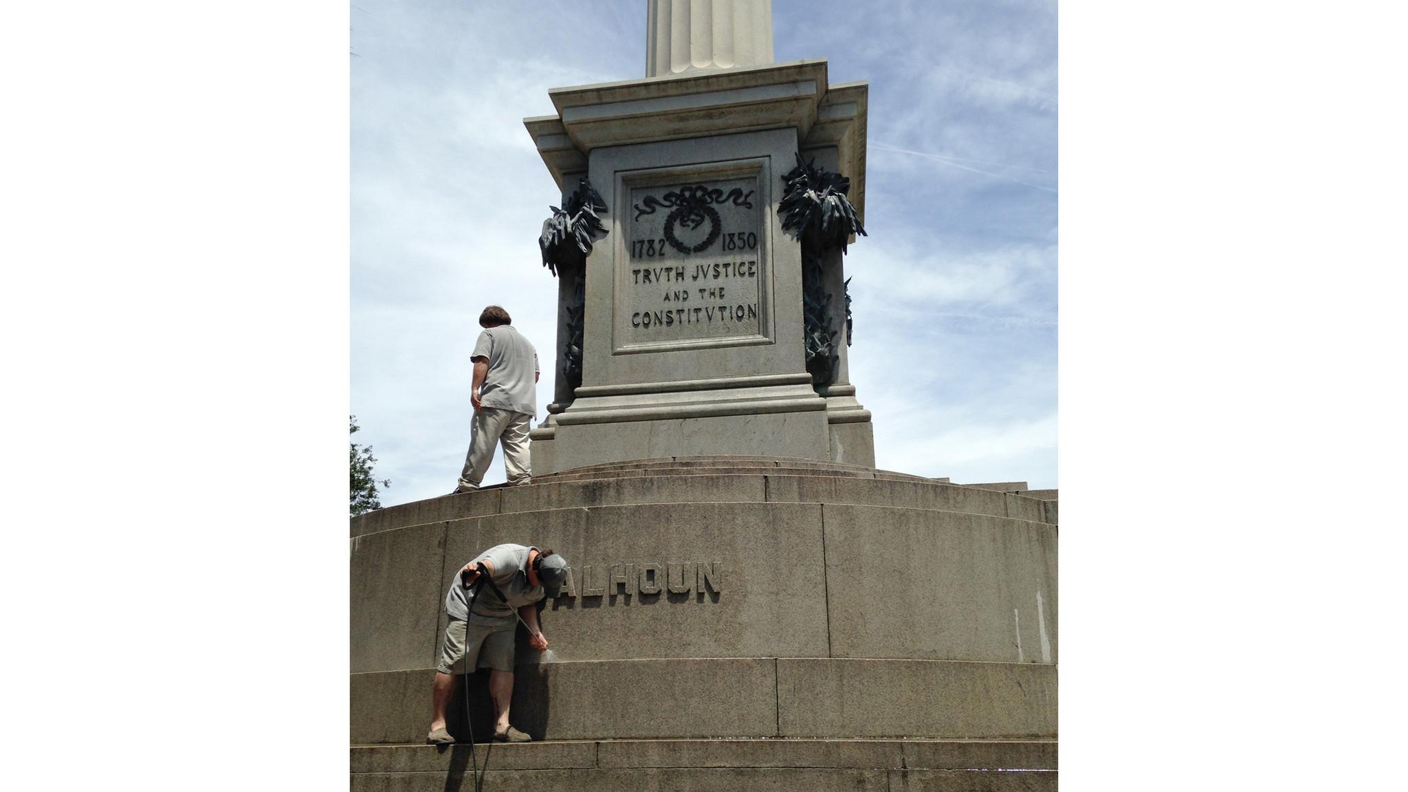 A June 23, 2015, file photo shows workmen removing graffiti from a statue of John C. Calhoun in Charleston, S.C.