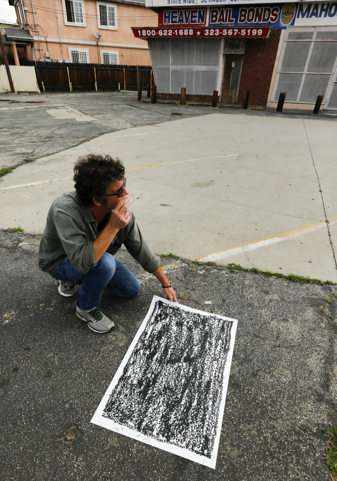 Artist Jeff Beall at the corner of Central Avenue and East 120th Street, in community of Green Meadows, with a rubbing that marks the site of an unsolved death.