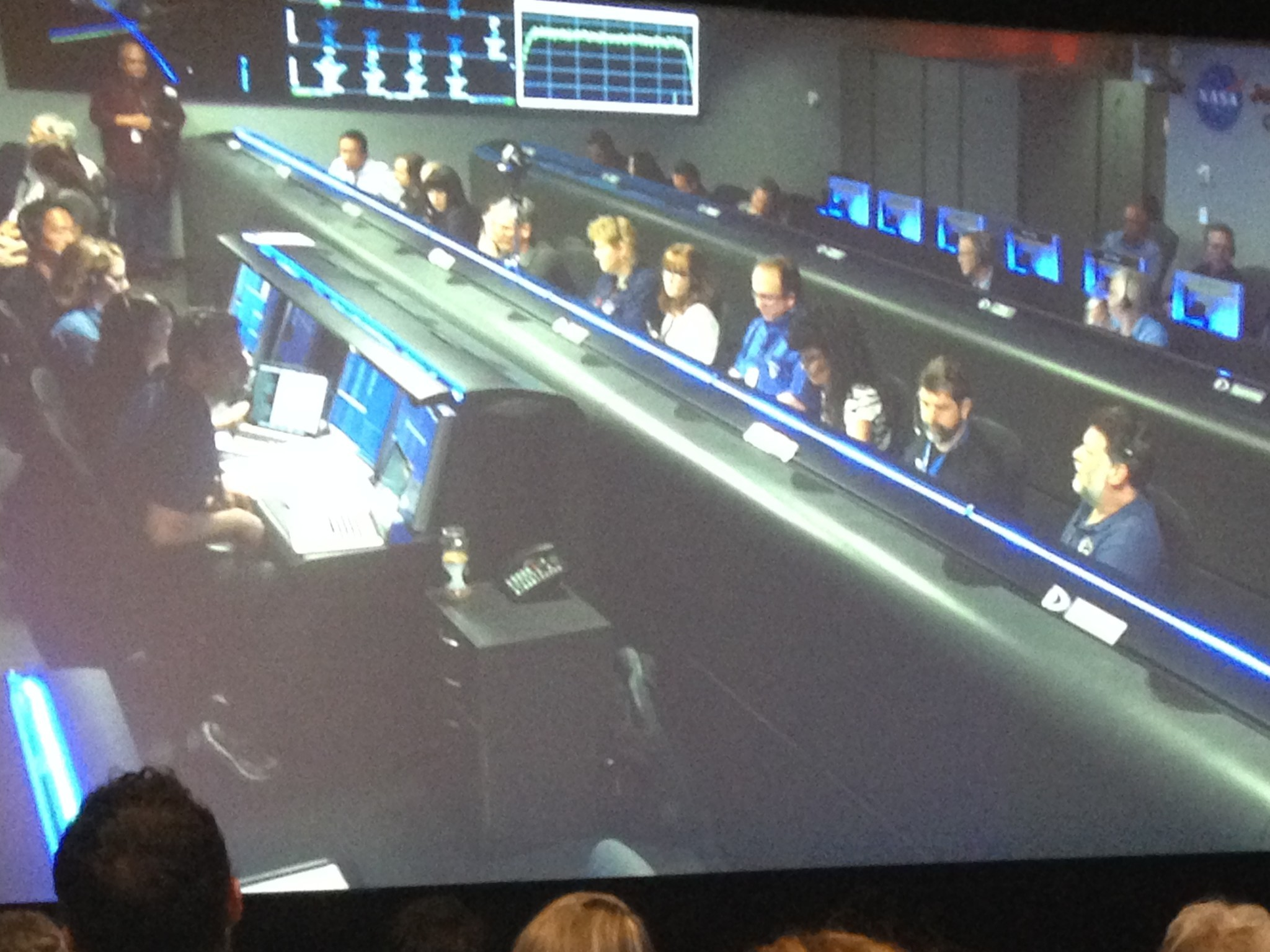 JPL employees (foreground) watch their colleagues on a screen as they all wait Cassini's signal.