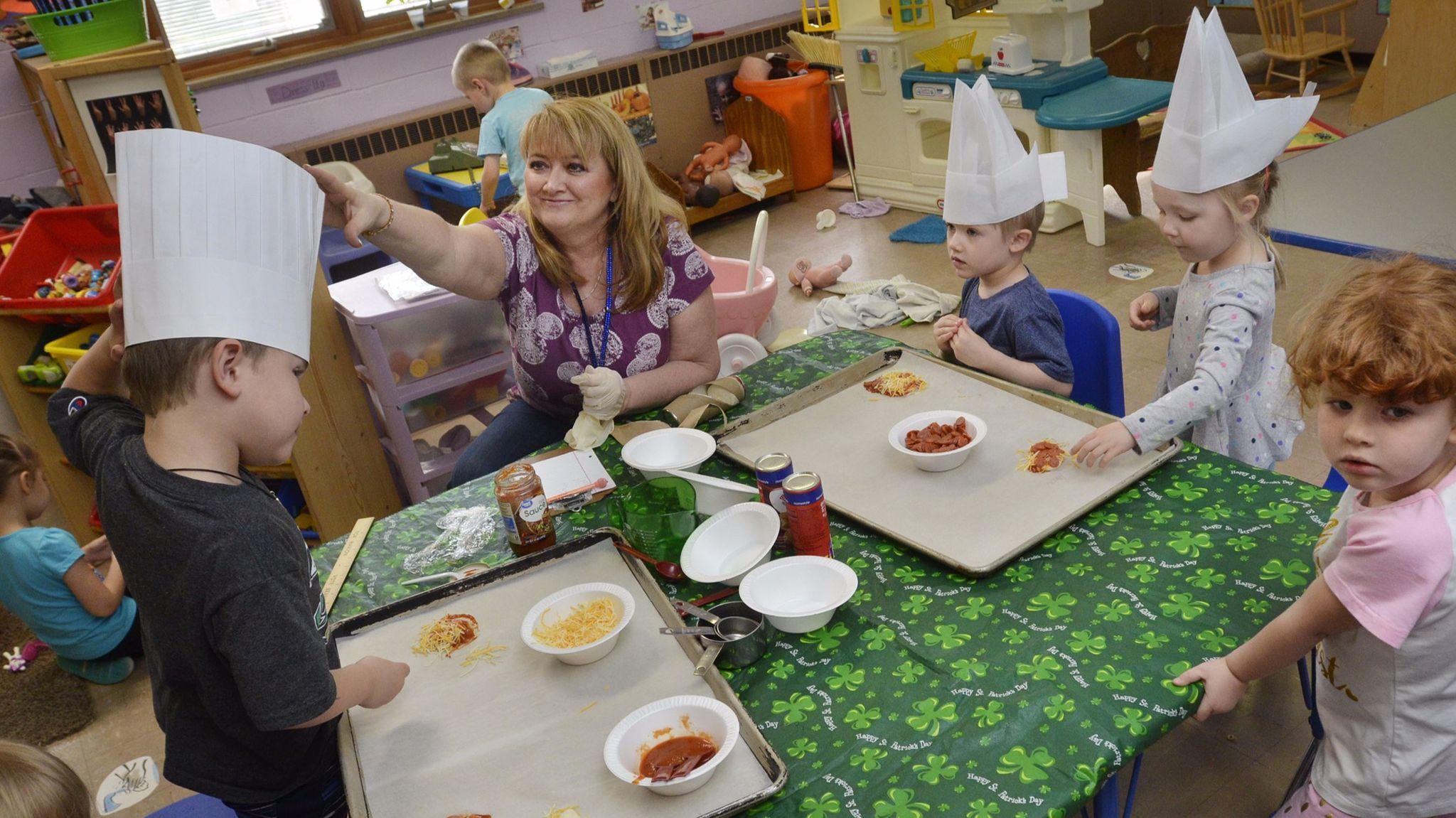 Teacher Debbie Kukuris-Milford helps preschoolers adjust their chef's hats and make pizzas at Westminster Preschool in Marion, Ind.