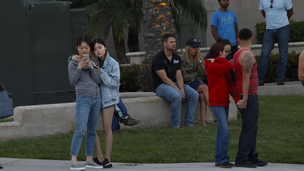 A crowd gathers at Golden Haven Drive and Judicial Drive in University City after a gunman shot seven victims at the La Jolla Crossroads Apartment complex.