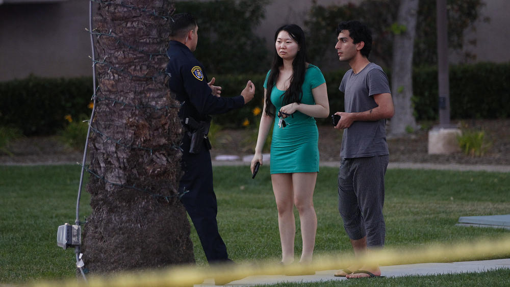 A San Diego police officer stops to question a couple near the area in La Jolla where a gunman is reported to have shot seven victims at an apartment complex.