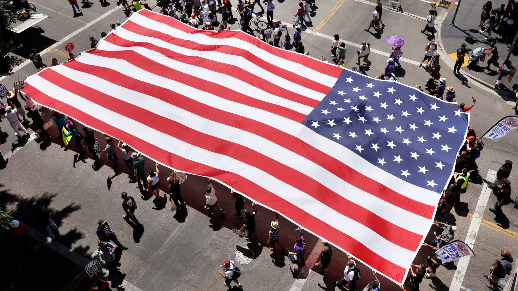 Marchers carry a giant American flag at the start of the May Day march that began at MacArthur Park.