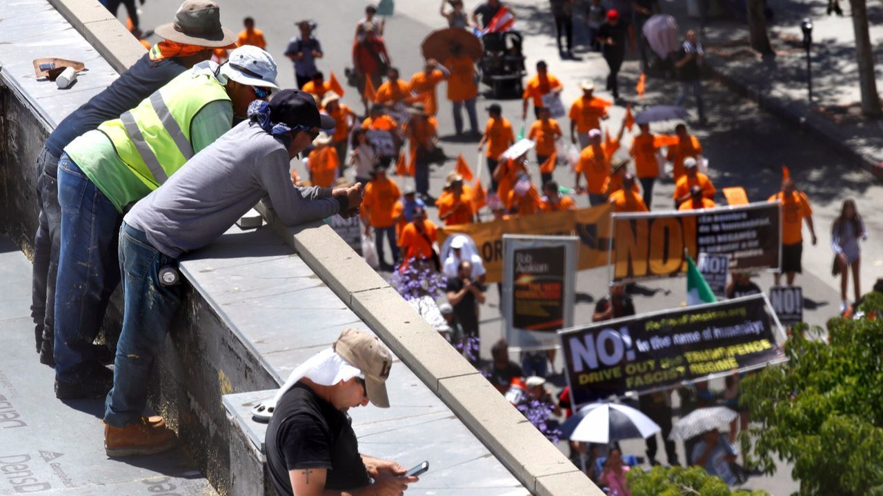 Workers take a break on a rooftop to watch a crowd of people marching on May Day.