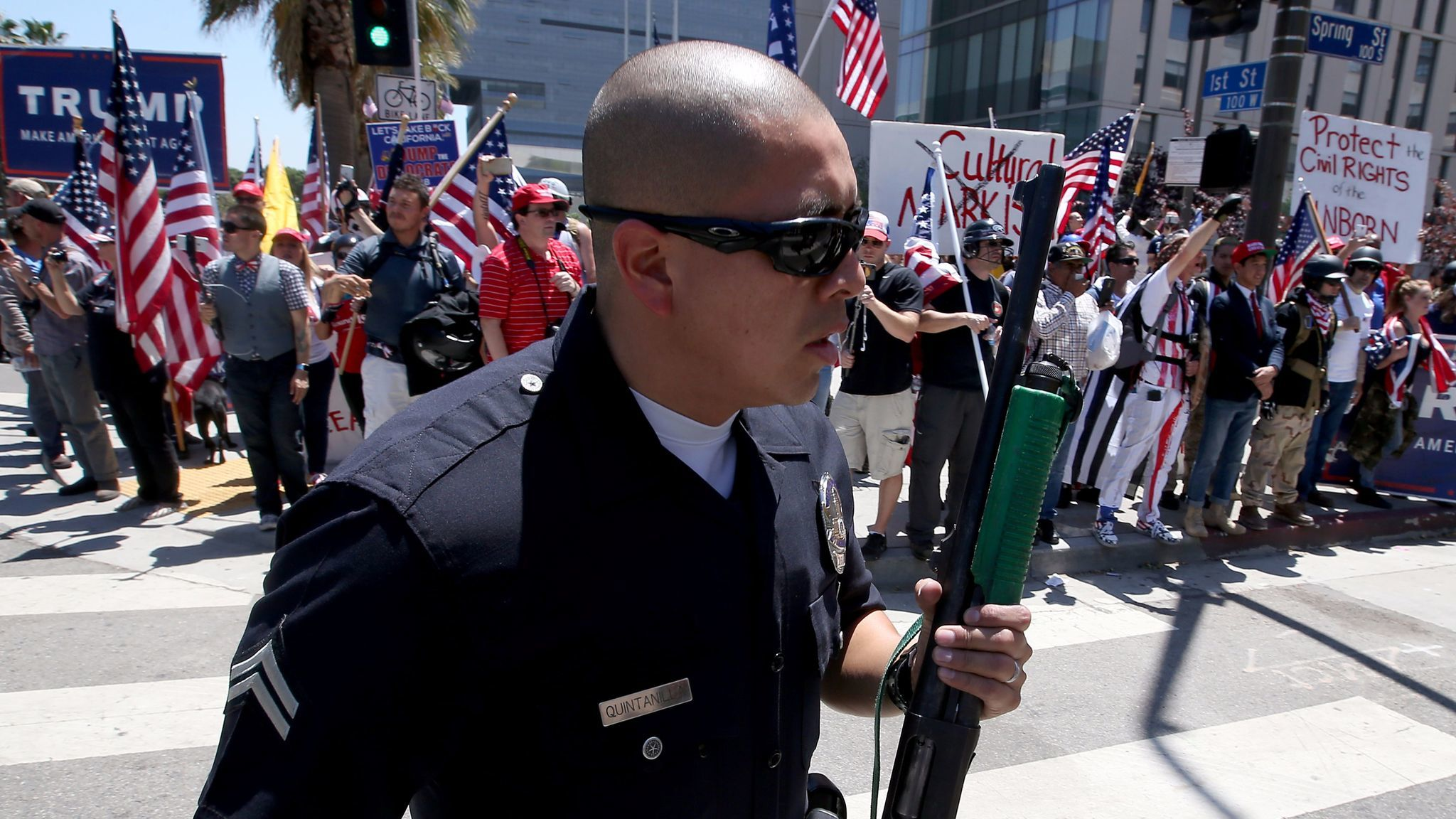 LAPD officers form a wall between pro- and anti-Trump protesters as they converge at 1st and Spring streets in downtown Los Angeles at the conclusion of separate May Day marches and rallies.