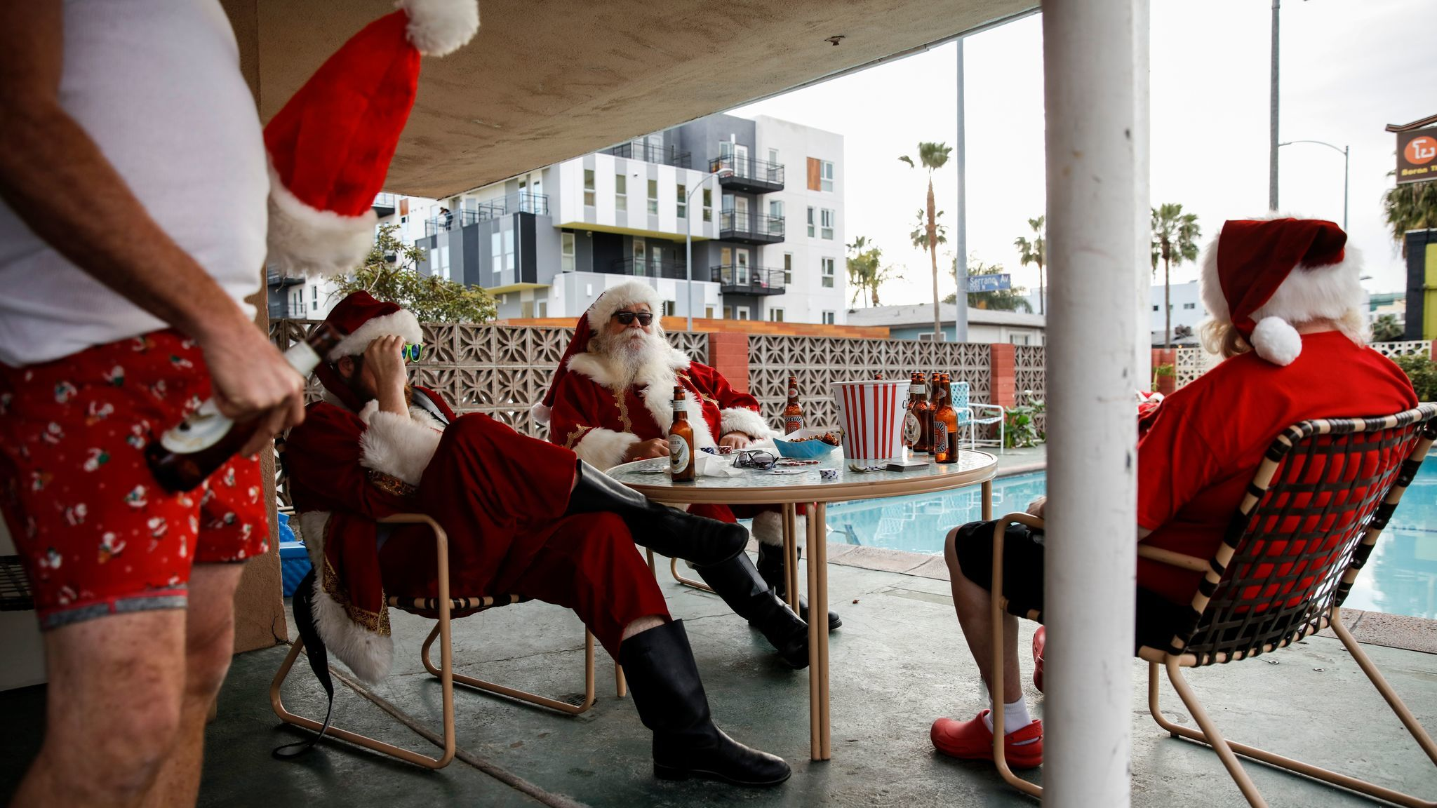 Background actors in Santa costumes get into position at a motel in Hollywood during filming of FX's