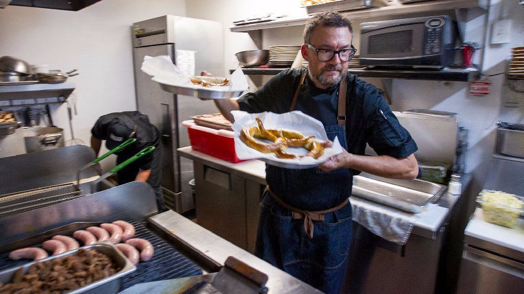 Thomas Curran, the co-owner of Taco Brat, prepares pretzels for guests during a tasting for his restaurant at the Harp Inn in Costa Mesa.