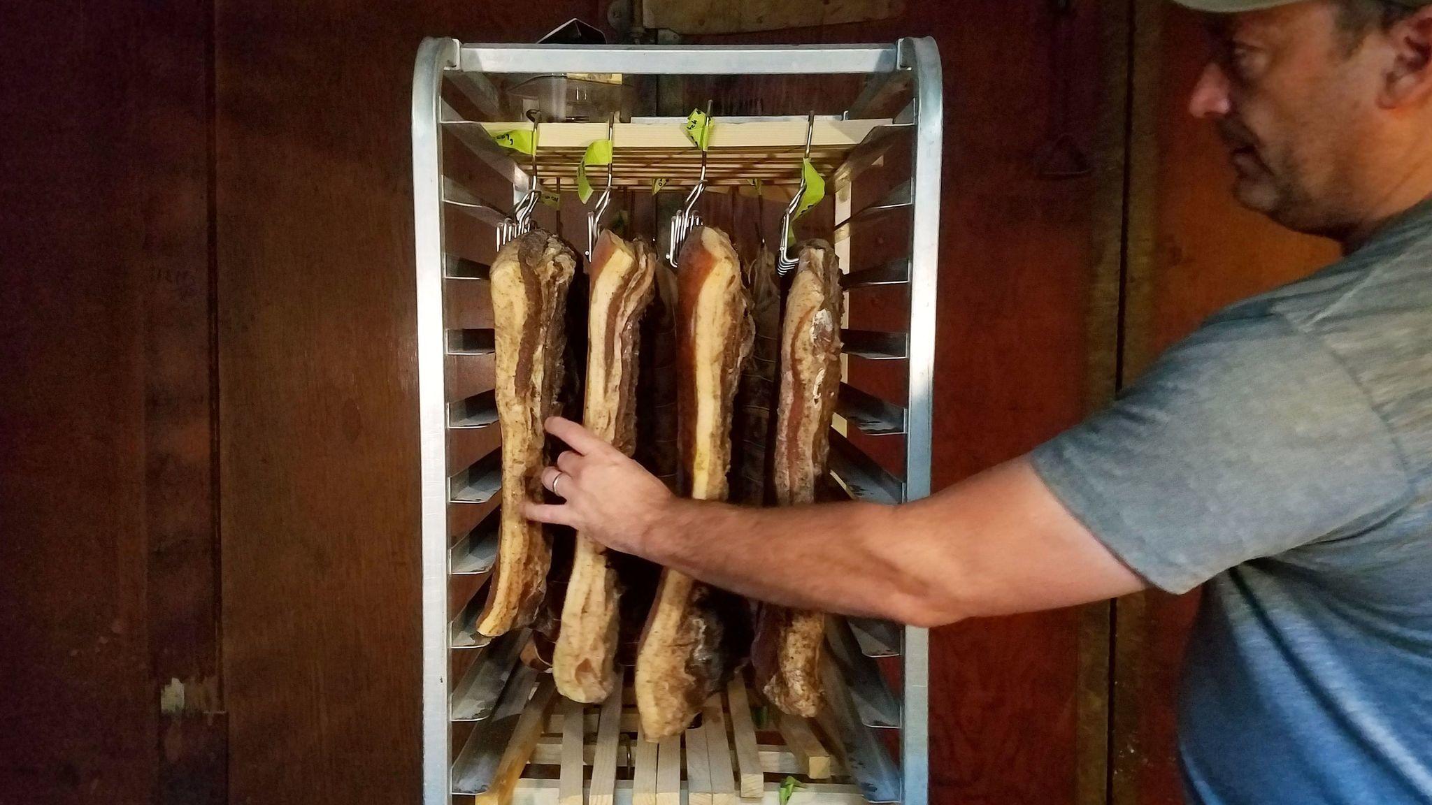 Chef Steve Samson checks in on some meat in the butcher locker at Rossoblu.