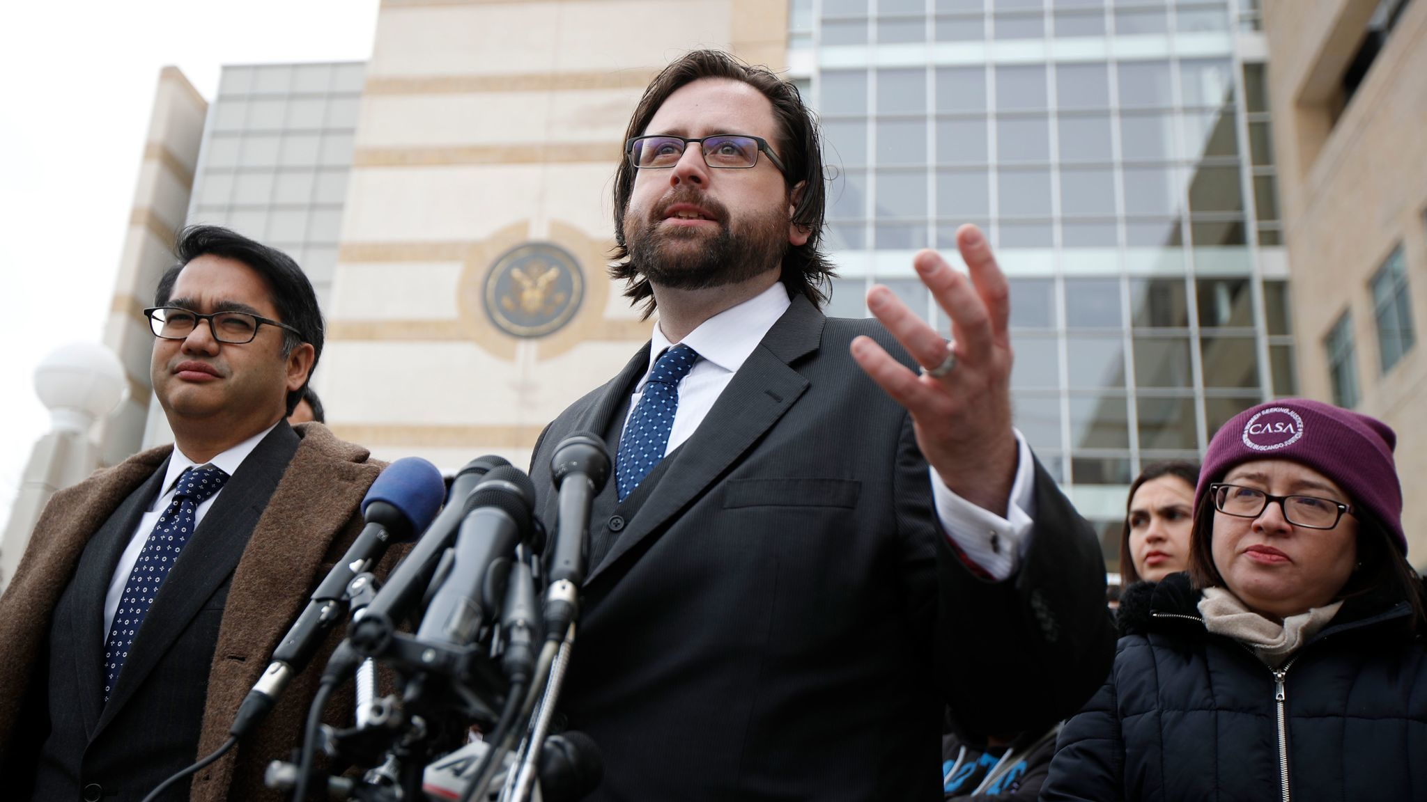 Justin Cox of the National Immigration Law Center, center, stands with Omar Jadwat of the American Civil Liberties Union outside the federal courthouse in Greenbelt, Md., after a hearing over the travel ban on March 15.