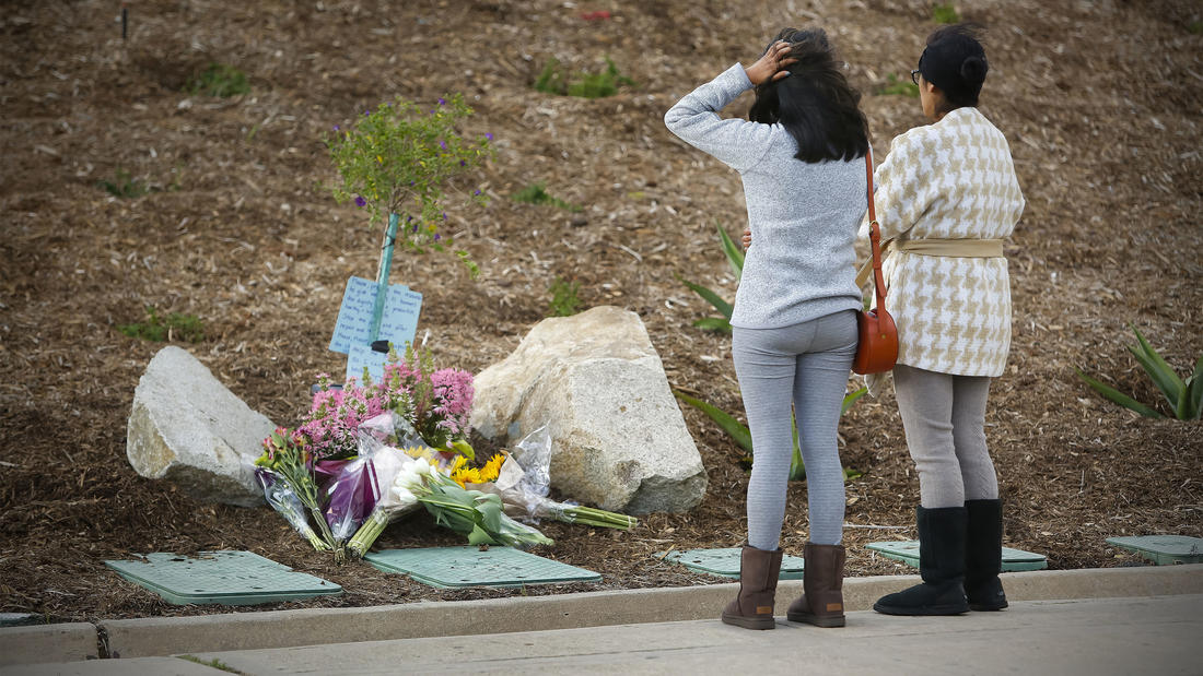 A mother and daughter pay their respects at a memorial of flowers that is starting to grow in front of Torrey Pines High School near where a 9th-grader at the school was shot and killed by San Diego Police officers.