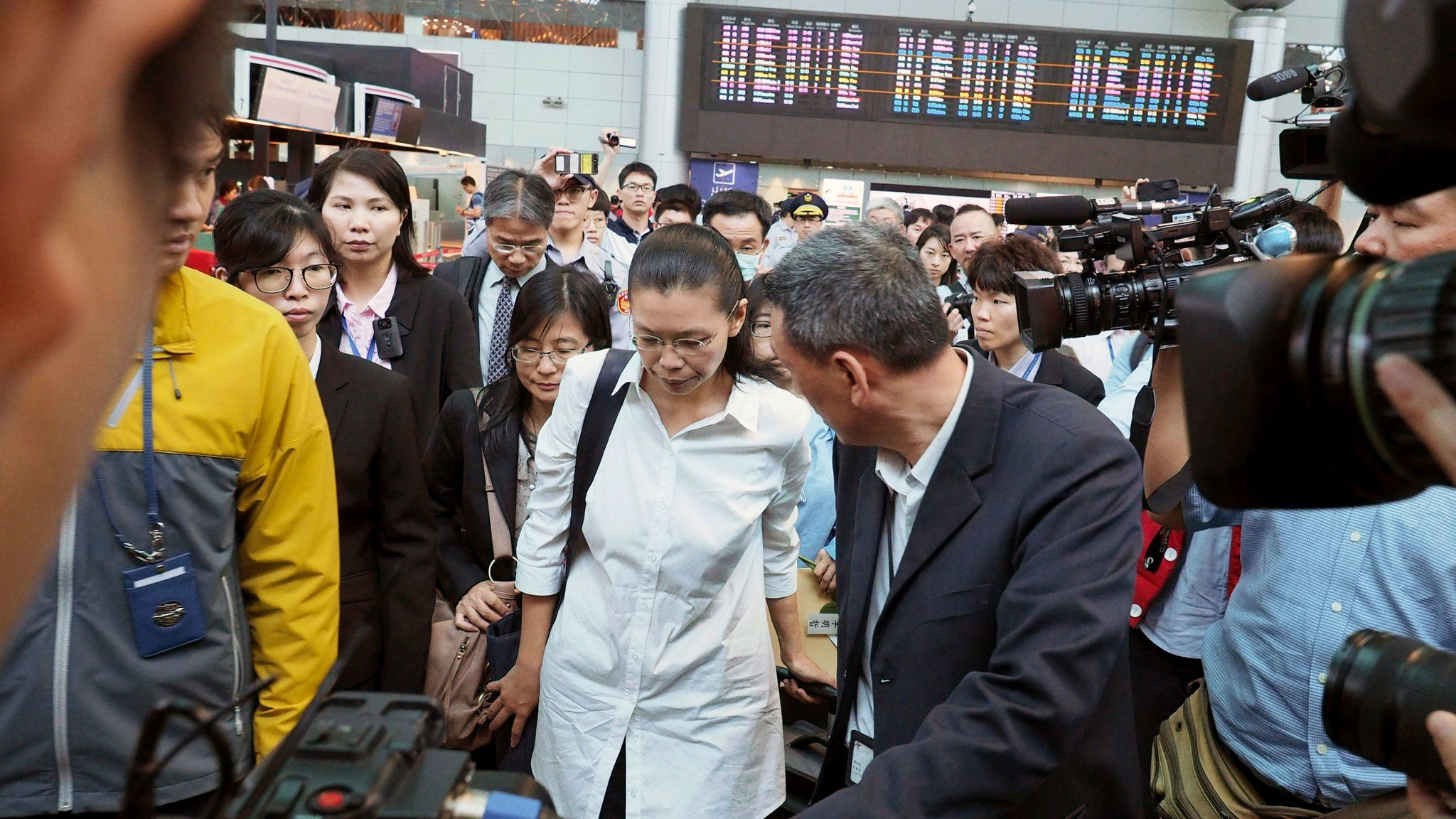 Li Ching-yu, center, wife of Taiwanese human rights activist Li Ming-che, who is being detained in China, leaves the Air China check-in counter at the Taoyuan International Airport in northern Taiwan on April 10, 2017.