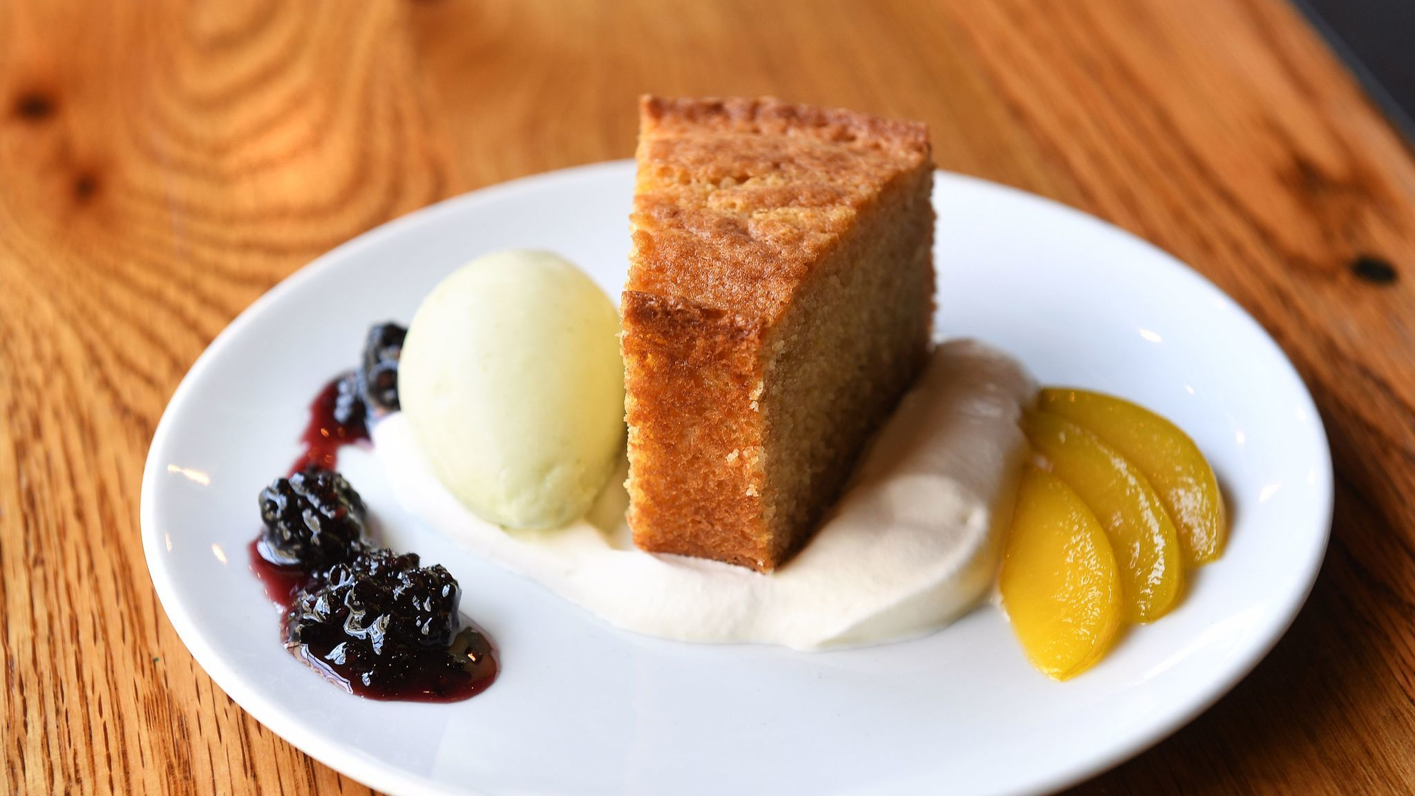 Einkorn buttermilk cake with lemon verbena and lemon sherbet, fermented blackberry jam and emerald plums is on the menu at Bestia in Los Angeles.