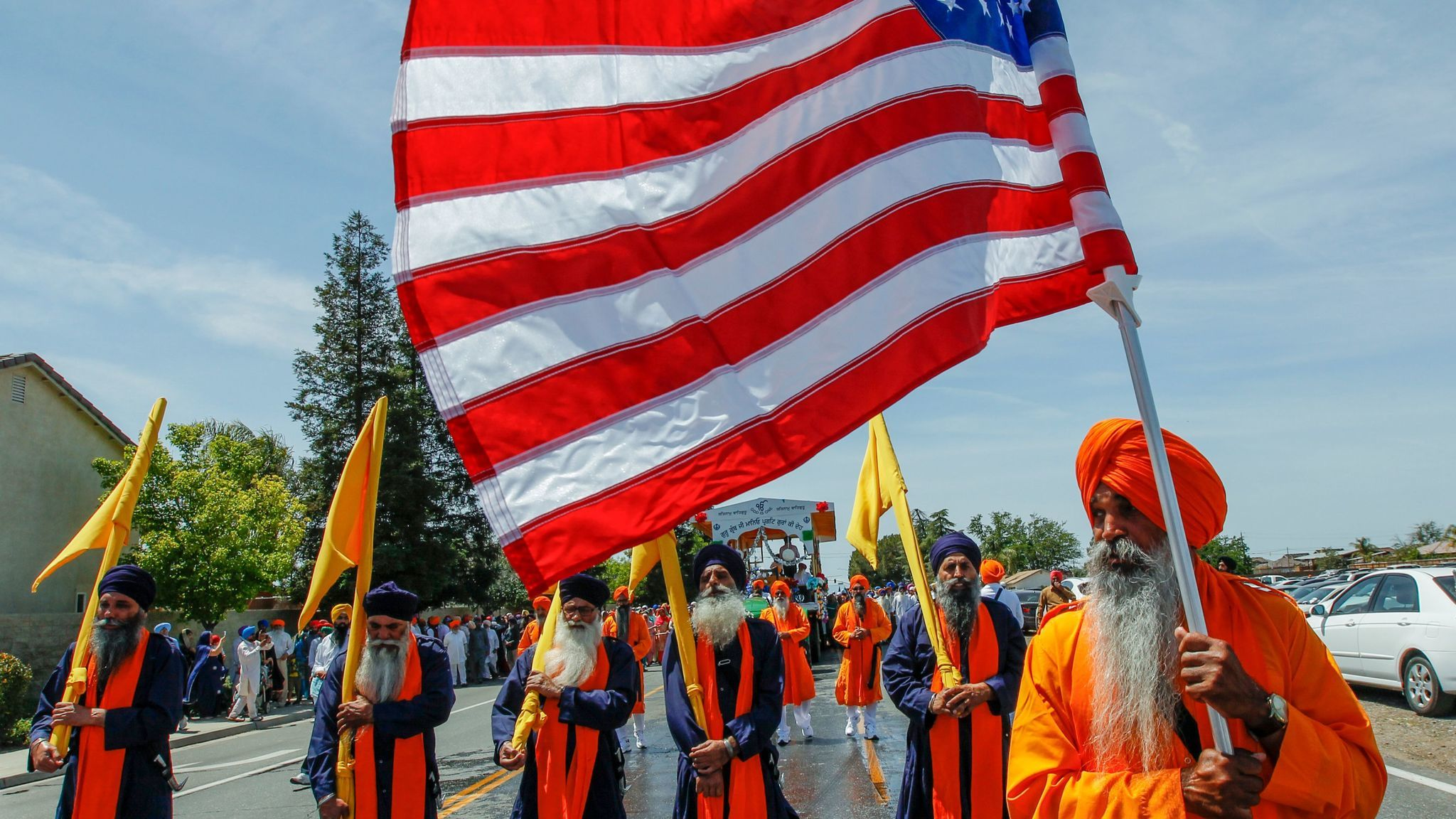 Sikh holy men walk in front of a procession carrying their holy book, Guru Granth Sahib, during a Nagar Kirtan parade.