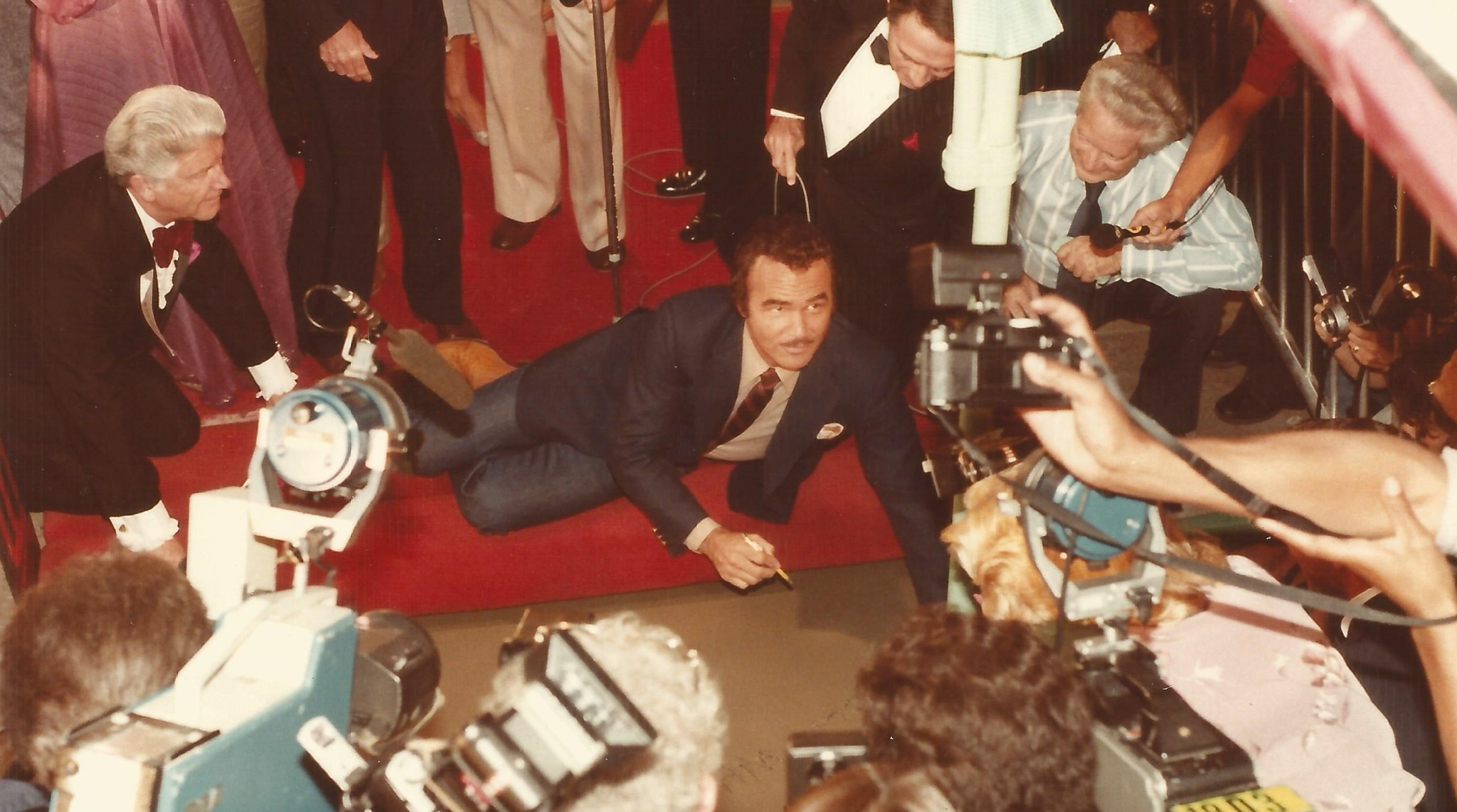 Burt Reynolds prepares to write in wet cement outside the Chinese Theatre in 1981.