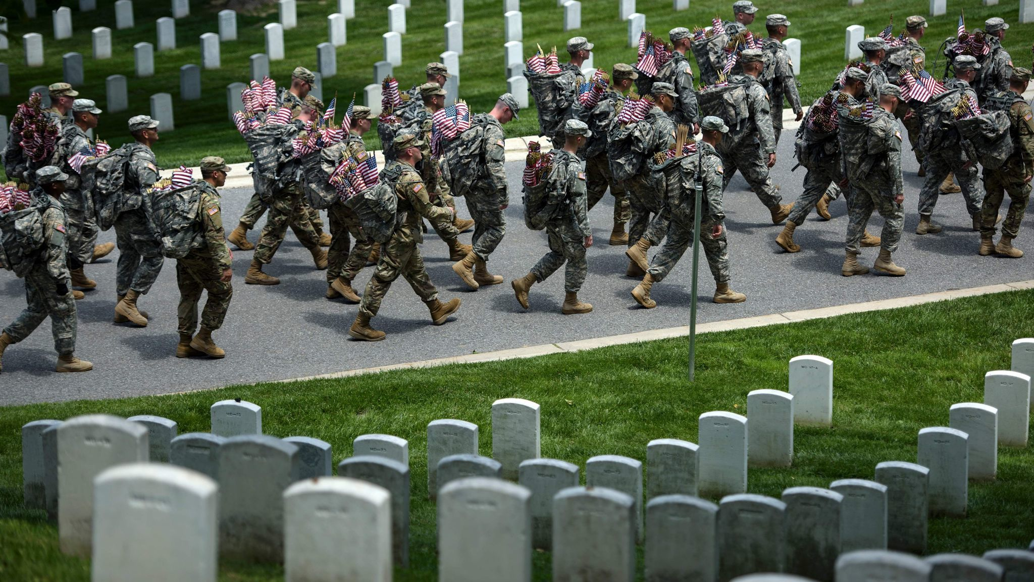 U.S. Army soldiers last year marched with miniature American flags that were placed at graves in Arlington National Cemetery in Virginia.