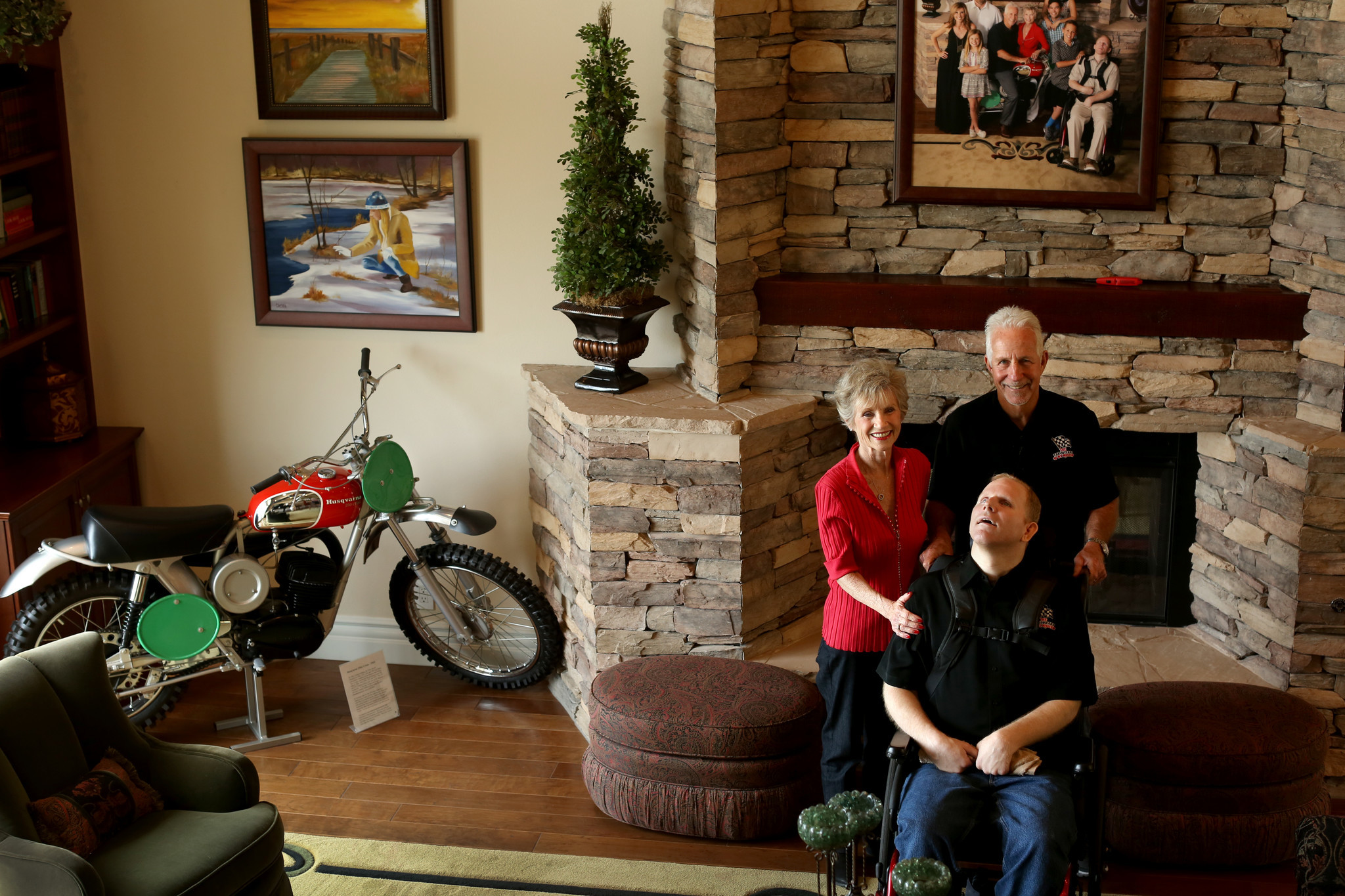 Tom White, with his son Brad and wife Dani in their living room, with one of his prized Husqvarna motocross bikes.