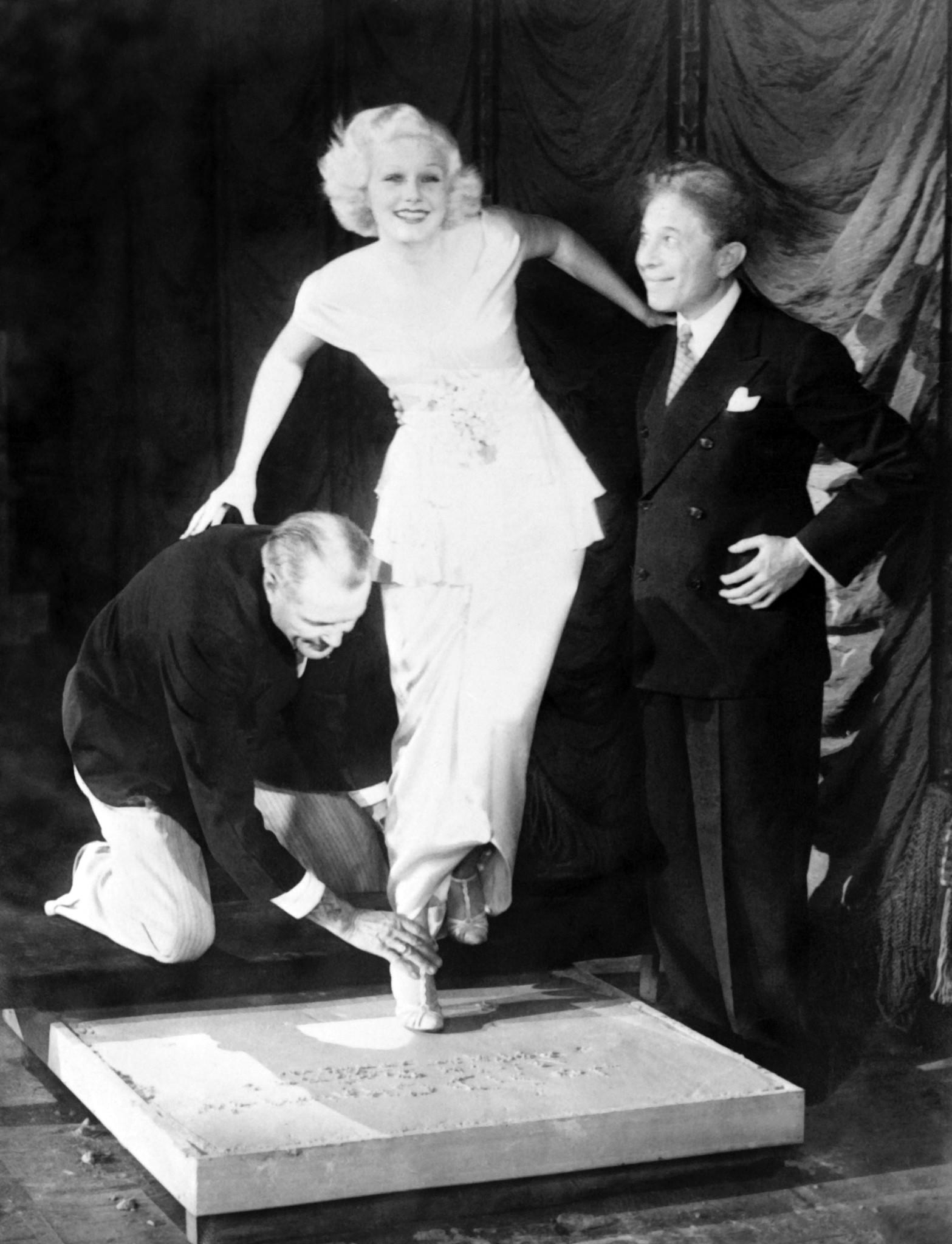 Sid Grauman, at right, takes Jean Harlow's footprint, at the Grauman's Chinese Theatre in Los Angeles, California, in 1933
